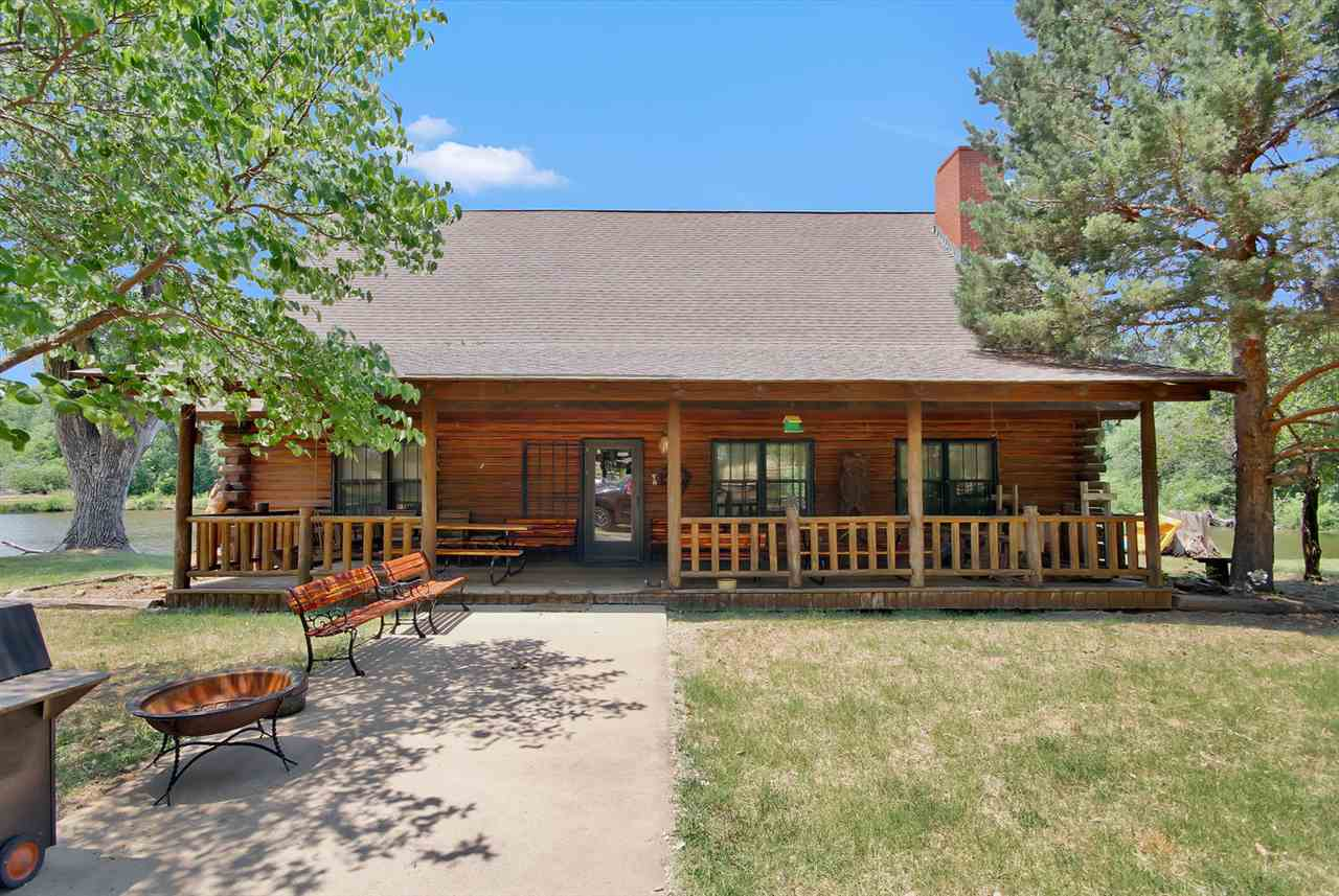 Private Log Cabin on 320 acres within 20 minutes of Hutchinson, 10 minutes from Arlington and only 50 minutes from WICHITA. This gorgeous fully furnished log cabin has a large open floor plan with 3 bedroom 2 and half baths and 25 ft vaulted ceilings.  And for your guests there is a fully furnished separate sleeping quarters that can sleep up to 6-8 people (kitchen and bath).   This very secluded retreat area has plenty of trees for that hunter with Box blinds for deer hunting and tri pods, couple corn feeders, quail buffer and the Heated Duck Blinds that can hold up to 6 people. This paradise has plenty of pheasant, duck, geese, quail, turkey and deer and of course ponds for the fisherman.  2 huge out buildings with John Deer Gator and a Camouflage EZ Go that stay with this incredible resort. 203 acres of incoming producing farm/crop.   Your horses will love the horse barn that can hold up to 3-4 horses and has a tack room.  This paradise is a hunter/fisherman's dream.  Listing agent is related to the sellers.