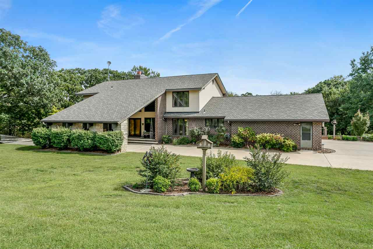 STUNNING 5 bed/3.5 bath home with impressive & unique architecture. Nestled among the trees on 46.9