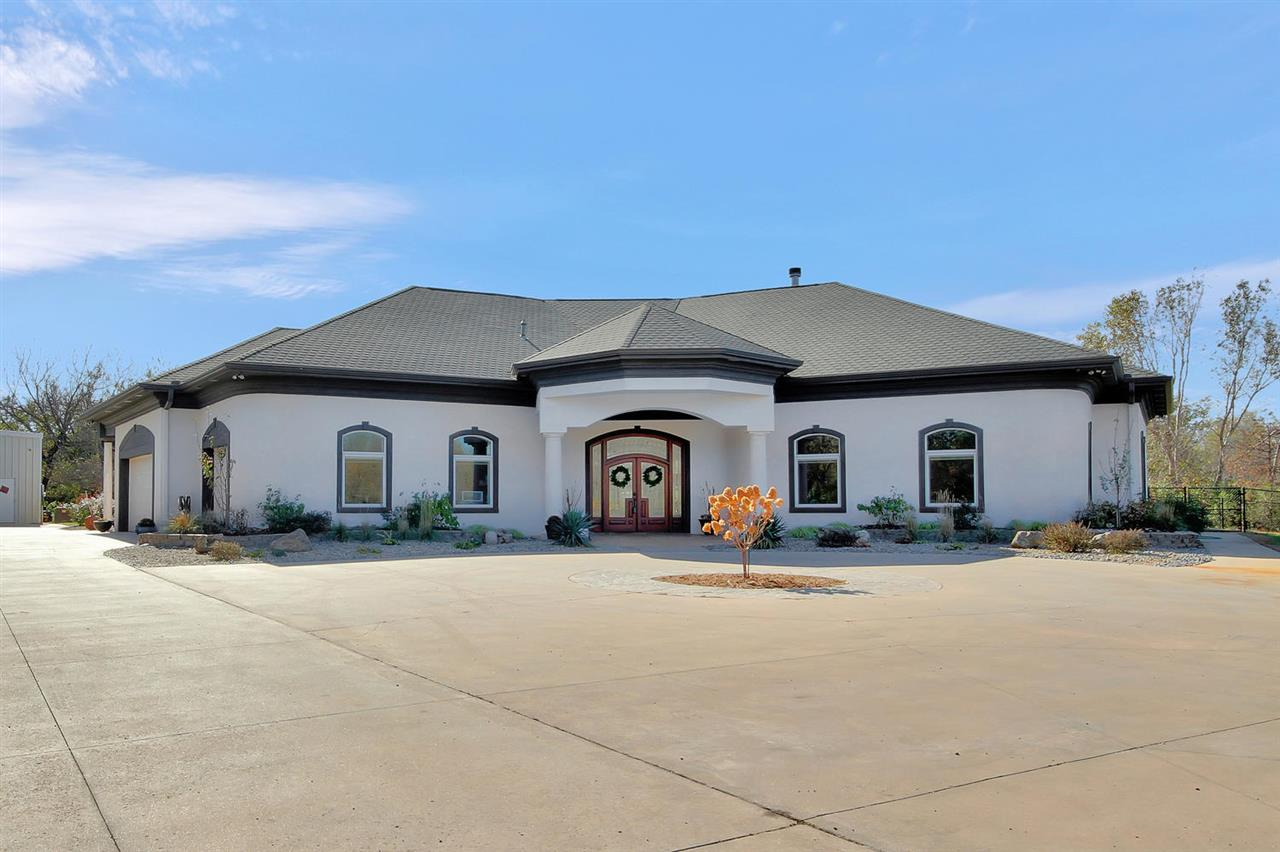 "This is a rare fine to come across a newly built, zero entry home on almost 18 acres of wooded oasis tucked off paved frontage within minutes of shopping and all the comforts of city life. When you drive down the treed drive you would not even realize you were still in the Wichita/Valley Area from the beautiful trees. The seller loved that this home had that true West coast Contemporary feel with having almost 6,000 sq feet of living space on one level and no stairs coming in from any entry to allow the homeowner to live here for years to come with no concerns. The wildlife is abundant on this land with plenty of room for ATV's and toys and little to upkeep with mowing. For the outside enthusiast, there is a large 60x40 insulated outbuilding at the end of the paved drive just beside the side load attached garage complete with 220 electric, large bay door (large enough for a camper or a bus),speaker system, concrete floor, and even an attached spray bay for body work inside the detached outbuilding. This home sits right off paved frontage road which is a major plus for the car enthusiast but with no noise back on the acreage. Now for the inside of this custom built ICF home, you will not believe the upgrades that were added to this home until you enter. This ICF built home has 6"" thick walls of concrete with Nurablock insulation surrounding and R-47 blown into the attic to provide an energy efficient home where sellers electric bill on average runs $300. Everything in this home was built to be a true custom design from radiate heated flooring that runs throughout most of the main level, central vac, 25x15 basement concrete room off the garage for storm shelter, zero entry access throughout the home, 9' doorways throughout the home with 12' ceilings, custom moldings and upgraded crown throughout the home, Pella windows with blinds inside the glass, and so much more. The home spares no lack of amenities with an exquisite coffer ceiling in the main living room with adde"
