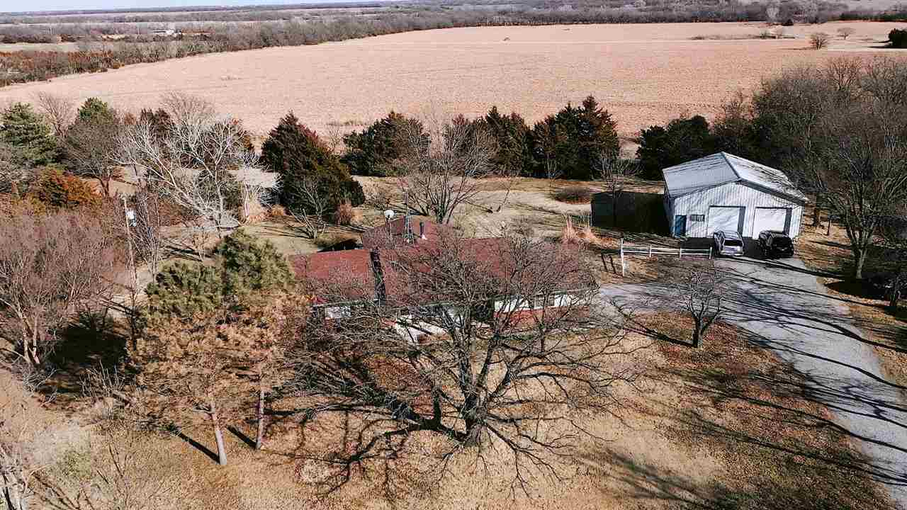 Once in a lifetime opportunity home to own. 10 acres on paved road blessed with tons of mature trees and two outbuildings. Sellers are down-sizing and now is a great opportunity to take over. The current sellers have done 10's of thousands of upgrades and maintenance to this residence. New wood Pella windows to be installed, newer roof, new exterior paint, improved lagoon and septic systems and newer heat pump system. The first building is 36 x 36 and includes concrete floors, 75,000 BTU heater, air conditioning and insulation and two 10 ft doors. There are horses allowed and also included is pipe fencing and an invisible fence for pets. The second building includes 3 horse stalls. Per Derby School District a student can request a transfer into the school district instead of Mulvane schools.