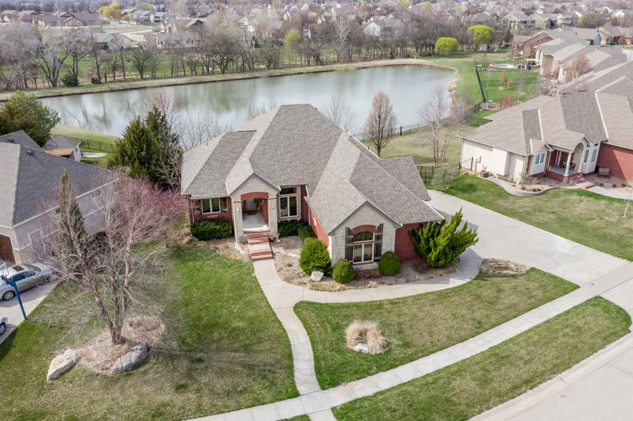 Welcome home to this Gorgeous Lake lot Custom Built Ranch in The Prestigious Bel Arbor Estates, Derby.  Professional Landscaping by Hong's with a Sprinkler System on a Well.  Home Welcomes you with a Sidewalk from the 3 Car Side load Garage and also a sidewalk from the the Street.  Covered Front Porch opens to Large Tile Foyer.  BRAND NEW CARPET through out the entire 3791 Square feet including Designer carpet on the stairs to the Full finished Walk out Basement complete with a Large entertaining Wet Bar, 2nd Fireplace 2 more Full Bathrooms with a Split Bedroom Plan.  Tons of Storage including a storm Shelter room.  Home Has a Gourmet Kitchen with Granite Counter tops, Pantry, Stainless Appliances, Real Wood Floors, Custom Drapes, HUGE Dining Space plus room for Bar stools at the counter tops. Kitchen Walks out to Covered Deck with Gorgeous views of the Water and Walks down to spacious Patio.  This home also has Sealed Cement Floors, Attic fan, Built-in Shelves.  NO SPECIAL TAXES!, Seller will pay them off!!!!