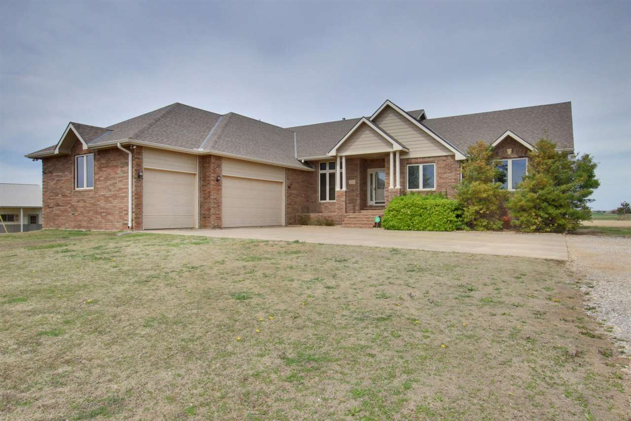 WELCOME Home to this beautiful,full brick, 3300+ square foot, 5 bed/3.5 bath home with almost 10 acres just west of Wichita in a quiet area where you can relax and enjoy life after a hard days work, away from it all! This home is beautiful and well built, in the highly sought after, Cheney School District! You are welcomed by a covered front porch that looks out over acreage. Imagine, the quiet evenings on the deck with your favorite drink, or early mornings with hot coffee...The main floor has a spacious living/dinning room combo. You'll enjoy the fireplace in the hearth room and instantly love all the larger windows that offer much natural light and reminds you that you are away from it all!The kitchen area offers a large island and eating bar, with a separate pantry. The 3 car over sized attached garage, with beautiful built-In cabinets, opens right off the kitchen where there is a 1/2 bath, and a large mudroom/laundry room-so convenient. The kitchen also has an exterior door to a large, newly painted deck. Upstairs the Master Bedroom has a large walk-in closet, 2 vanities, and a soaker tub. There are two more bedrooms and lots of storage. If that's not enough, there is a full walk-out basement! While the basement is not completely finished, there are two finished bedrooms and a full bath.The basement is sheet-rocked, clean and ready for carpet/paint.The bar, fireplace, large storage room and you guessed it, more natural lighting will definitely be a plus!That's not all!!The shed is 30 X 70 with a concrete floor and plumbed for a bath. This home won't last long!!!!