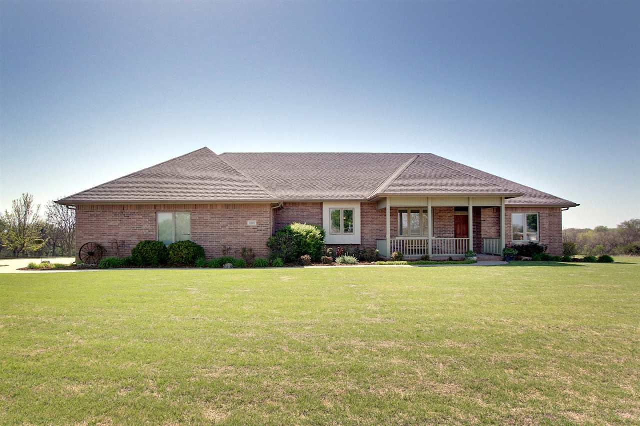 Have you ever wanted to live in the country, right off paved roads where you come home and just get away from it all? As you enter the gated drive that is paved also you will feel that way coming home here to 10801 N Meridian. See the sunsets off your screened in porch looking out over the beautiful pond with its own well and the lush treed acreage behind. You wonder if you just left the city, 5 minutes away. This home is located within 2 minutes of the highly, desired Valley Center schools and top of the line Valley Center high school and 5 minutes from town. The home was built new in 2005 with all the amenities you could imagine; zero entry access from garage and only one step from front door entrance, full brick exterior for less maintenance, solid hardwood floors throughout almost the entire 2215 sq ft of the main level, large upgraded casing throughout the entire home, large windows that look out over the pond with custom window treatments, and so much more. The home has a split bedroom floorplan on main level with 2 bedrooms each arranged like separate suite spaces that each have a view out to the water plus an additional main level office that could be converted to a 3rd bedroom if needed. A chef's kitchen with Thermador gas range, custom hood, walk in hidden pantry, custom wood cabinets, built in oven and microwave with lots of countertop space for prepping. The master suite on the South end of the home just received a remodeled bath complete with custom tiled walk in shower (zero entry) with barn glass shower door, double sinks with quartz countertops, sauna (that does not stay but underneath is rough in for freestanding tub), large walk in closet, and separate toilet room complete with urinal and toilet. As you head to the basement, you pass the gorgeous view coming in from the mid-level walkout access as the home has exterior access from here and off the main level from the screen-in deck. The basement has a large family room with great viewout windows to