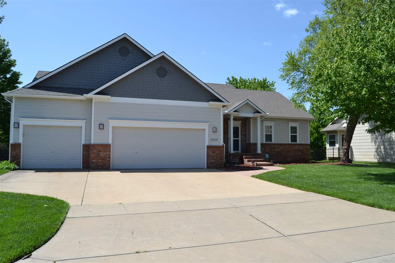 Must see this FANTASTIC home with 3100 square feet and open floor plan that enjoys views  to the screened in deck as you enter. Large picture windows include beautiful custom coverings that are easily adjusted to suit your day. The kitchen features granite counters and tile back splash open to the dining & living areas creating a great space for entertaining. The private master suite bath includes double sinks, custom vanity, beautiful walk-in tile shower and great large tub to relax in. It also has a large walk-in closet. The two upstairs bedrooms have easy access to the full guest bathroom. Main floor laundry is a plus which opens up to a 3 car garage with tons of storage!  The lower level includes 2 large bedrooms with walk-in closets, private full bathroom and a fantastic family room, fireplace and walkout onto a lower deck. A plus is the screened in covered deck which opens from the living room upstairs. It is complete with a wall mounted TV that goes with the home and a ceiling fan for comfort. Deck opens up to the backyard that has a large sport court and picnic party area.The neighborhood has stocked ponds, playground and walking paths and a MAINTENANCE FREE POOL THAT IS LESS THAN A BLOCK AWAY! There is also a sport court that has an in-ground bracket for a basketball goal. It can easily be converted to a pickle ball court or outdoor cooking area. Home is also wired with camera's through Cox Home Life Security and service can be transferred to the buyer. A plus is the Andover school bus picks up the kids in front of the neighbors home!  Home has the best of both worlds-lower Sedgwick County Taxes, NO SPECIALS  & Andover Schools!  Call for your private showing today.
