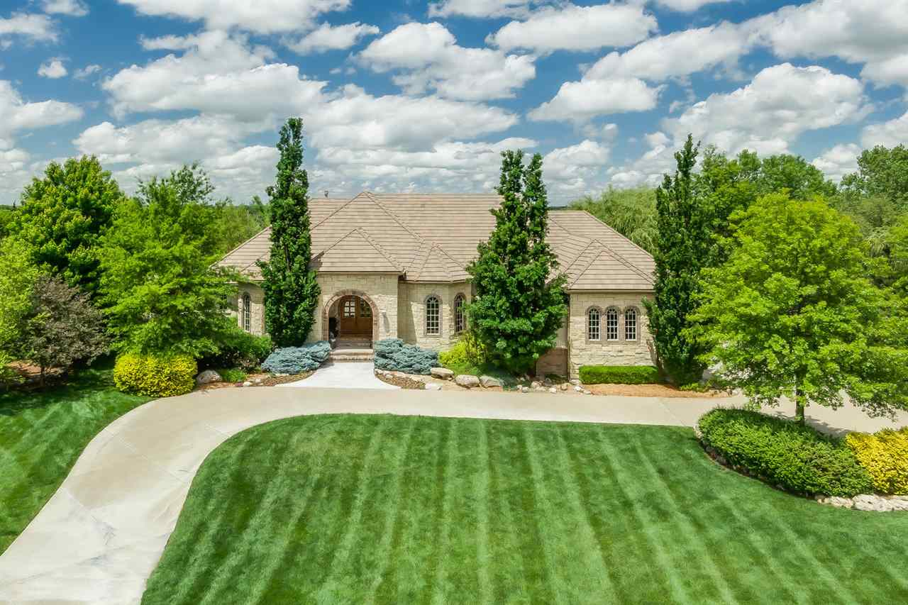 Exquisite Flint Hills estate has a spectacular eye catching exterior with a 3 car side load garage,