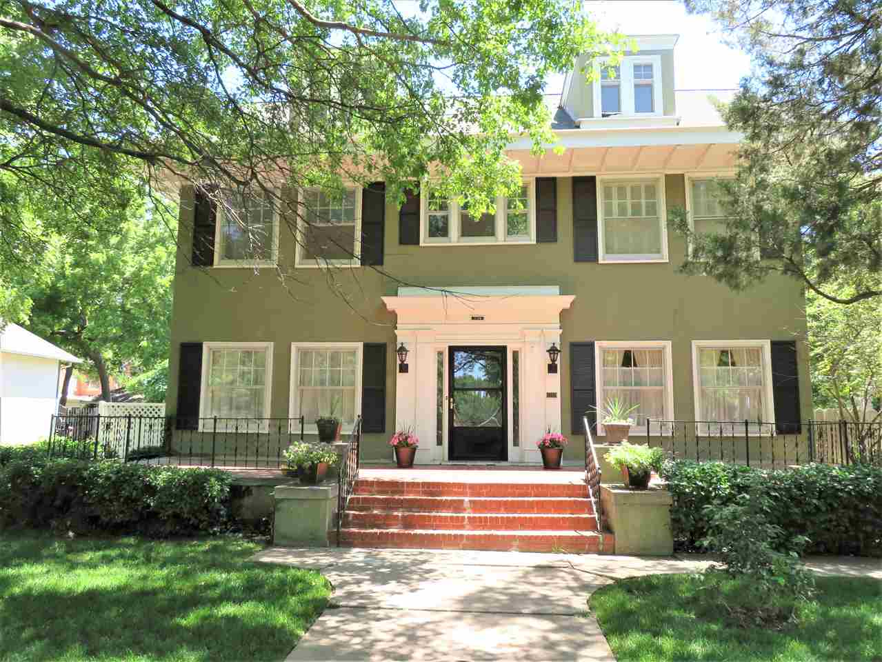 Rare opportunity to own a historic home on one of Wichita's most beautiful streets, Belmont Place, between the arches! This 1914 gem has only had four owners, the first being Fern Mead Jordan, the widow of one of Wichita's founders, J.R. Mead and the last having owned the home since 1969. Walk into a huge entry with a classic center hall floorplan highlighted by a gorgeous open staircase. There are 10+ foot ceilings in the large living room and dining room which are both perfect for entertaining and are filled with natural light. The living room (32' long) is spacious and is anchored on the east end by a lovely fireplace. This home has been lovingly cared for over the years and retains many original fixtures and a sophisticated décor that lends itself to the age of the house and harkens back to the glamorous era of 1930's Palm Beach. The main floor also includes a bright and airy kitchen with large pantry, back staircase, and half bath~ perfect for guests.  Upstairs you will find three large bedrooms with original hardwood floors, walk in closets, a sunny enclosed sleeping porch (ideal for a home office, nursery or 4th bedroom) and a large full bath with many original features and plenty of storage. There is an extra abundance of storage space to be found with the huge unfinished (yet could be) basement and attic. The private back patio and side yard provide endless possibilities to create your own outdoor secret garden. There is currently a sport court which needs repair or can easily be taken out and replaced with a southern exposure lawn and garden. There has been slight settling over the years which is reflected in some walls but is common with the age of the house, but the bones and structure and integrity appear solid and beautiful. There is a small yearly HOA fee ($175 annually)  for the residents of Belmont Place to maintain the arches at Douglas & Central as well as the original electric streetlights along the four-block stretch. Don't let this opportunity