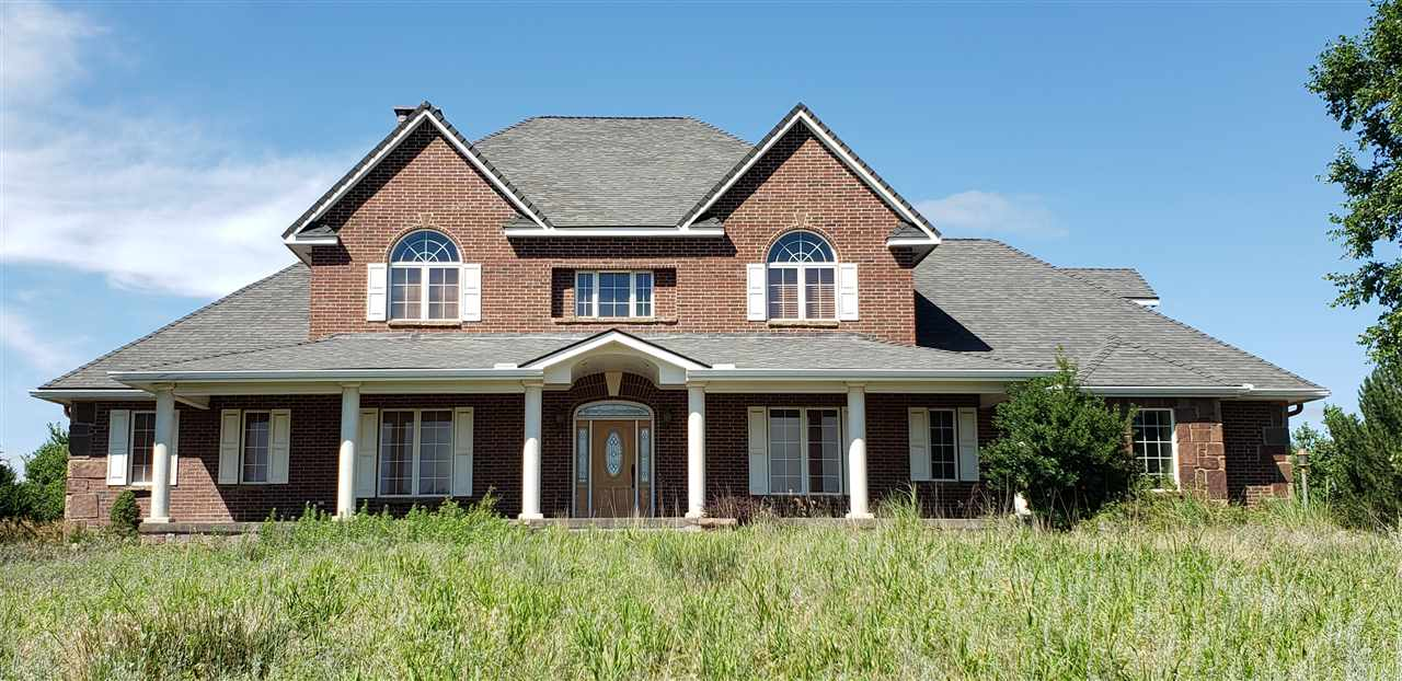 Come see this one of a kind grand, custom built home on 43 acres in a secluded and private location in Reno County. This spacious listing offers your growing family or multi-generational families six bedrooms and four- and one-half bathrooms. The layout includes a main floor master bedroom with a luxurious en suite of his and her sinks, his and her cedar lined closets, granite countertops and glass block shower. The main level also includes a large and cozy family room with nineteen-foot ceilings, stunning floor to ceiling slate fireplace, beautiful foyer, versatile office or library and a formal dining room.  For the cook in your family there is a gourmet kitchen with full slab granite island, walk-in pantry, butler's pantry, stainless steel appliances and commercial grade oven. Large main floor laundry right around the corner from the kitchen. Inviting sunroom under the covered deck. The second story provides three more bedrooms, one full bathroom and a large walk-in storage/linen closet. In the fully finished, view out basement you will find stained concrete floors, two more bedrooms (one en suite), another full bathroom, family room, game room, bar/kitchenette area, theatre room, fireplace and large safe/storage room. There is also a second washer and dryer hook-up. Energy efficient central heat/air with closed loop geothermal and central VAC. Also includes a steel built, 70' x 60' barn/shop with automatic doors. Property selling as-is. In-ground swimming pool inoperable.
