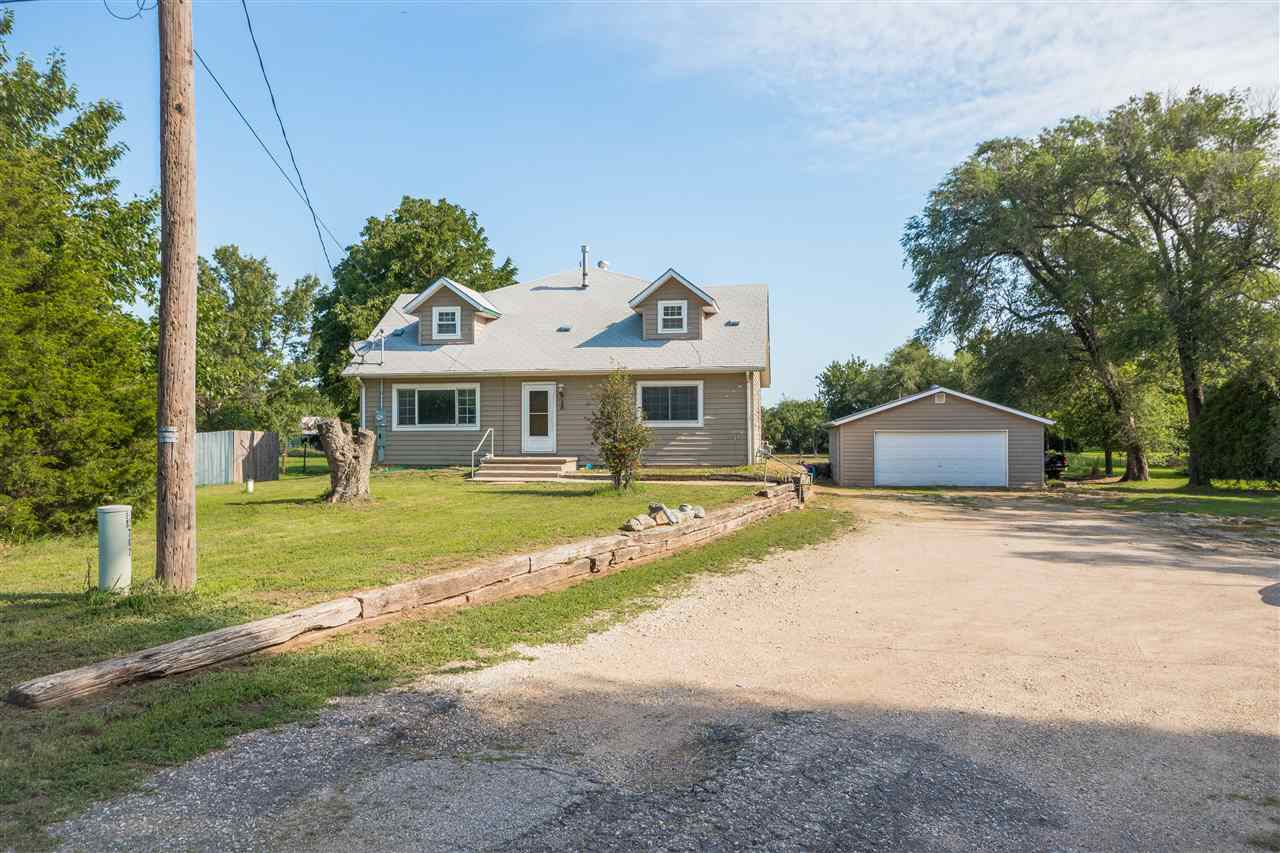 Country-esque 1.5 story home within the Haysville School District and situated on close to a 1 acre