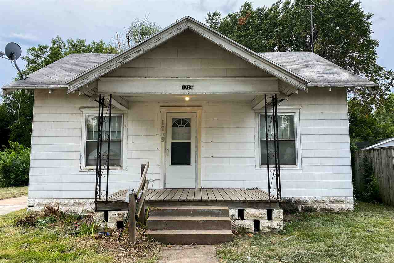 This bungalow home features a covered front porch with a storm door and security light. There is a l