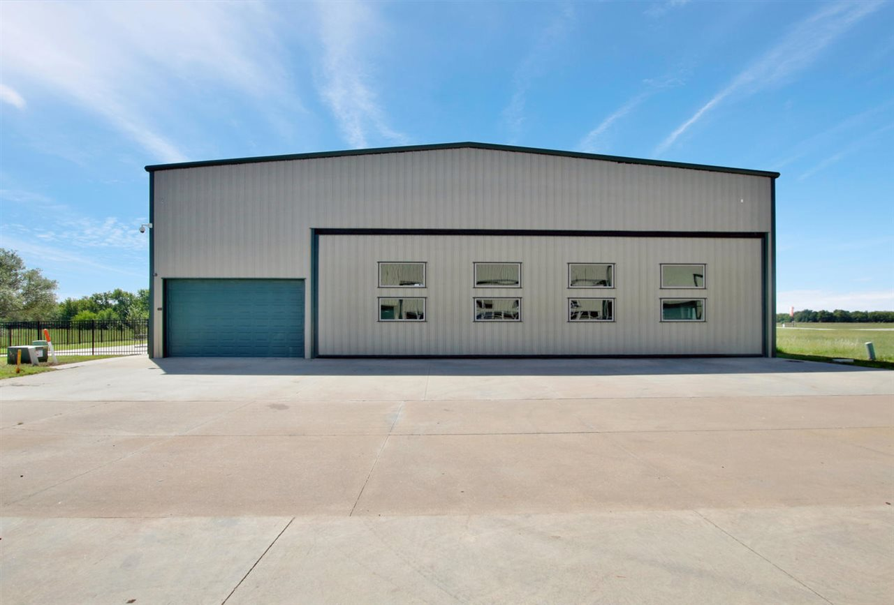 A brand new and very exciting listing I have today is a beautiful, one owner, custom built home nestled inside a huge airplane hanger at the Benton airport in Kansas. Just less than 20 minutes away from my office, which is at 13th St and Webb Rd. All paved roads to the front step of the house. The hanger can house 1, 2 or 3 planes depending on the size of the planes. I will meet you there in person to show you and tell you all about it. The house itself is constructed with high end materials and finishes. Lots of natural light, loft living feel yet spacious and very classy. Double iron front doors, high ceiling, open staircase, large rooms, huge master bedroom and master bathroom with big shower and jetted tub. Big kitchen with large island, granite counters and high end stainless steel appliances. A guest room with its own entrance, comes with its own bathroom, almost like a second master bedroom suite. Every bedroom has its own bath and large closet. Upper level has sliding doors lead to a modern balcony connected to a separate staircase that leads to the hanger floor. Plantation shutters, beautiful flooring, very cool light fixtures and ceiling fans. Upper floor family room is plumbed for a big wet bar for entertaining or family use. There is a full size kitchen set up in the hanger for entertaining or family gatherings. Two big sliding doors lead to a very nice pool with automatic cover and totally updated to the best pool equipment. Fenced back yard. Living full time at the hanger is super fun, you have the best of both worlds, modern living standard yet so close to nature and you can jet in and out of Wichita and no one ever knows. This property is also perfect for weekend home.