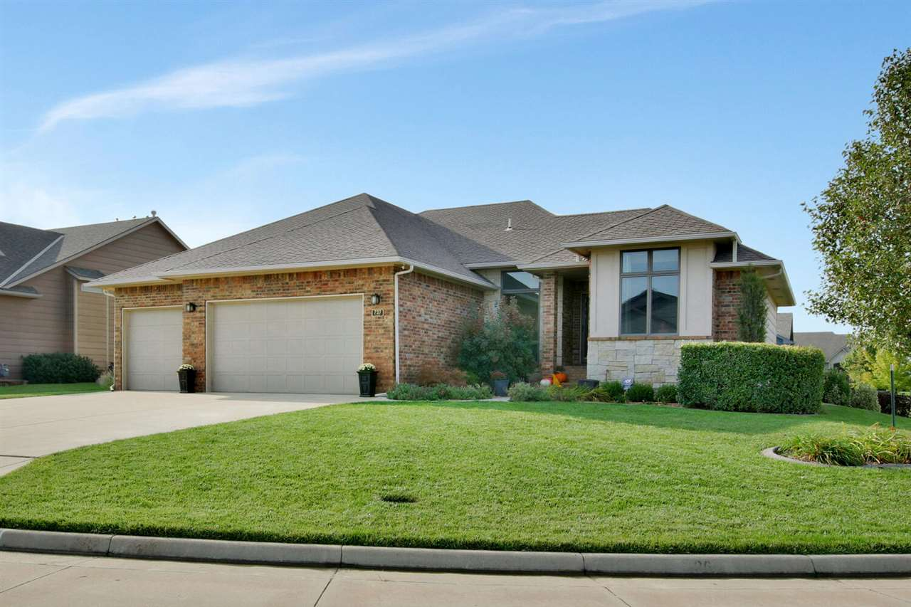 This beautiful 5 bedroom home is situated on a corner lot in Newton's desired Sand Creek Station Development. Just 20 minutes north of Wichita and borders an award winning golf course with private area swimming pool. The seller paid off the specials when they purchased, so NO SPECIAL TAXES! A popular open floor plan with a split bedroom set up. Gorgeous kitchen, maple woodwork, granite counter tops, walk in pantry, eating bar, all stainless appliances including a stainless double oven. Dining area leads to a covered deck perfect for grilling out! Hard wood floors and cut out for buffet hutch. Living room with built ins, fireplace and big windows for natural light. Master suite includes the closet of you dreams ATTACHED to the laundry room for easy access! Master bath with double vanity, granite counters, soaker tub and separate shower.    Basement is fully finished with view out windows, fireplace, built-ins, large rec room, beautiful wet bar with wine cellar, 4th and 5th bedrooms and full bath as well as TONS of storage! The landscaping is lovely and includes a large stamped concrete patio with stone border. Over sized composite deck, sprinkler system and irrigation well make this yard easy to maintain and enjoy. Spacious 3 car garage.The area is in close proximity to shopping, dining, YMCA and Newton Medical Center.