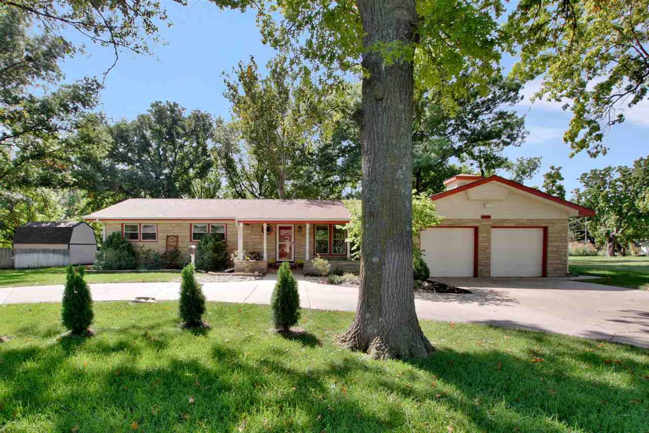 "Incredibly appealing Ranch home that sits on 3/4 Acre on the West edge of Wichita! From the street, you'll first see the circle drive and covered front porch complete with swing! Step inside and you'll find beautifully maintained living areas. The formal living room leads to a 33' kitchen & dining area that is the heart of this home! With plenty of room for large gatherings, this ""Cook's Delight"" Kitchen features beautiful Corian hard surface counters, stone backsplash, huge center Island with Jenn-Air cooktop and separate wall oven, tons of workspace as well as storage, PLUS a nice pantry! Just off the kitchen is a main floor family room with cozy wood burning fireplace for cooler weather ahead!. You'll love the great views of the backyard from the family room! There is a large main floor laundry that exits to the garage. Just off the kitchen is a screened patio that will be the perfect, bug-free spot to enjoy the outdoors. The home features a large master bedroom with private bath, as well as two additional bedrooms and bath, on the main floor. Basement is finished with a nice sized rec room and two additional finished rooms perfect for office, sewing room or even your home gym! The backyard of this home is so stunning. Fully fenced yard, giant shade trees, two storage sheds, and the cutest log sided cottage that is finished and includes a heat and cooling source. You will truly love this home! Don't delay--set up your private showing today!"