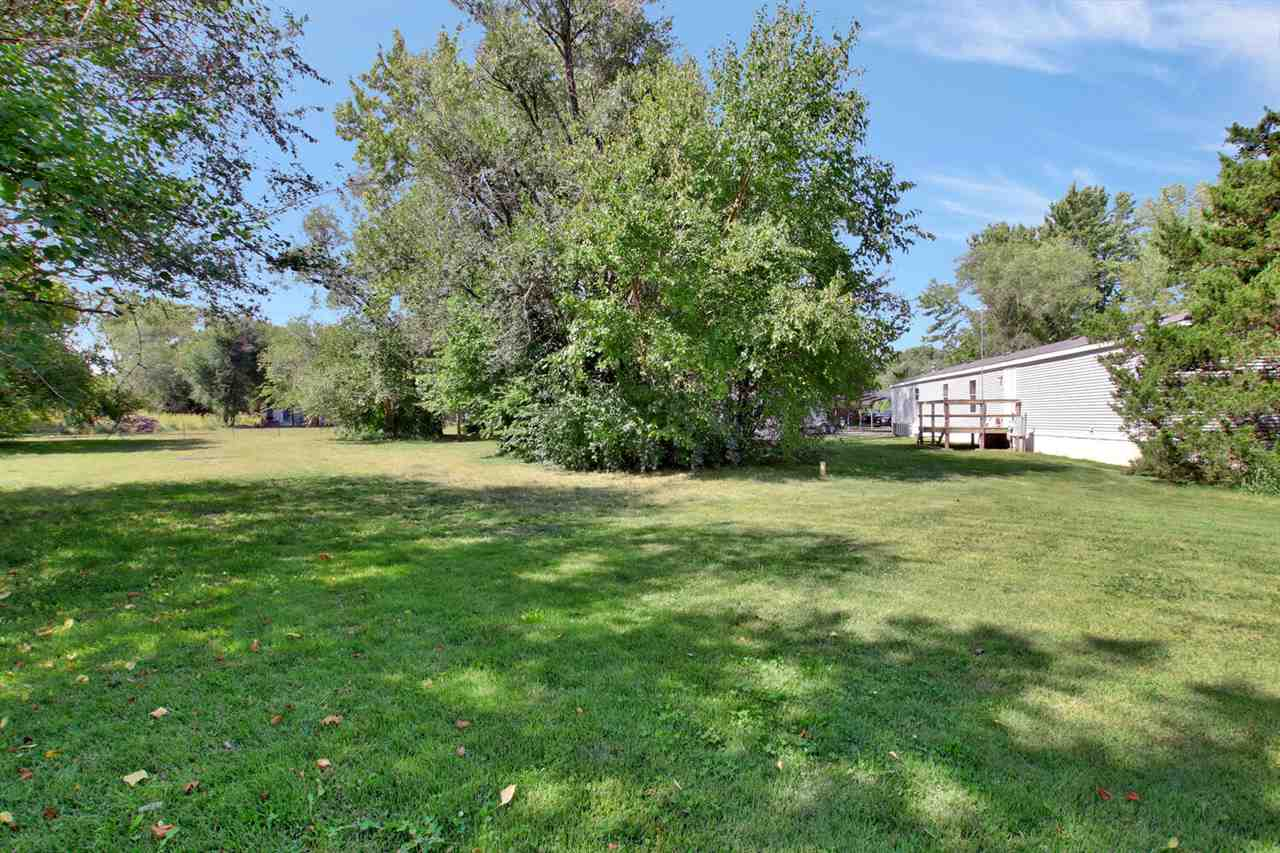 Home is tucked behind a tree row and feels like your own private paradise. Just under an acre lot, y