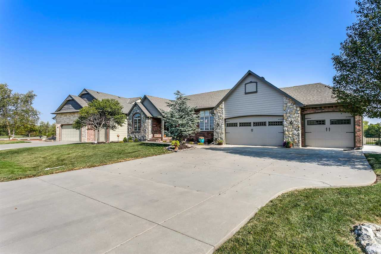 This home is in the desirable Bear hill Estates with easy access to 1-35 and on the bus route for **VALLEY CENTER SCHOOLS**this home has 4 bedrooms plus a non-conforming bonus room in the basement ,  3 full baths, a backyard you won't want to leave, and **NO SPECIALS TAXES**! The main level features a floor to ceiling decorative fireplace, kitchen with granite counter-tops, pantry, pull-out drawers and an eat-in nook with spectacular views of the lake and access to the large composite deck, brand new hardwood floors throughout the main floor, New carpet throughout the entire house, this home has also been recently painted inside and out. The laundry room features a large utility sink. Being a formal model home you can enjoy working on projects all year long in the fully insulated, painted, heated and cooled over-sized garage with lots of storage! The basement has a huge family and rec room. Featuring another fire place, wet-bar and view-out windows to the backyard. You will also find another bedroom, bathroom, storage and a finished bonus room with cabinets. Walk out of the basement into the covered patio pit up to the rock sitting area. The yard backs up to the neighborhood lake which features a jogging path and decent fishing. Current owners installed a new wrought iron fence to keep the kid/pets in the yard. Landscaping in the front and backyard with soaker hoses and sprinkler system. This home has it ALL! All the work is DONE and ready for you to move in and enjoy!!!  See it fast before its Gone!