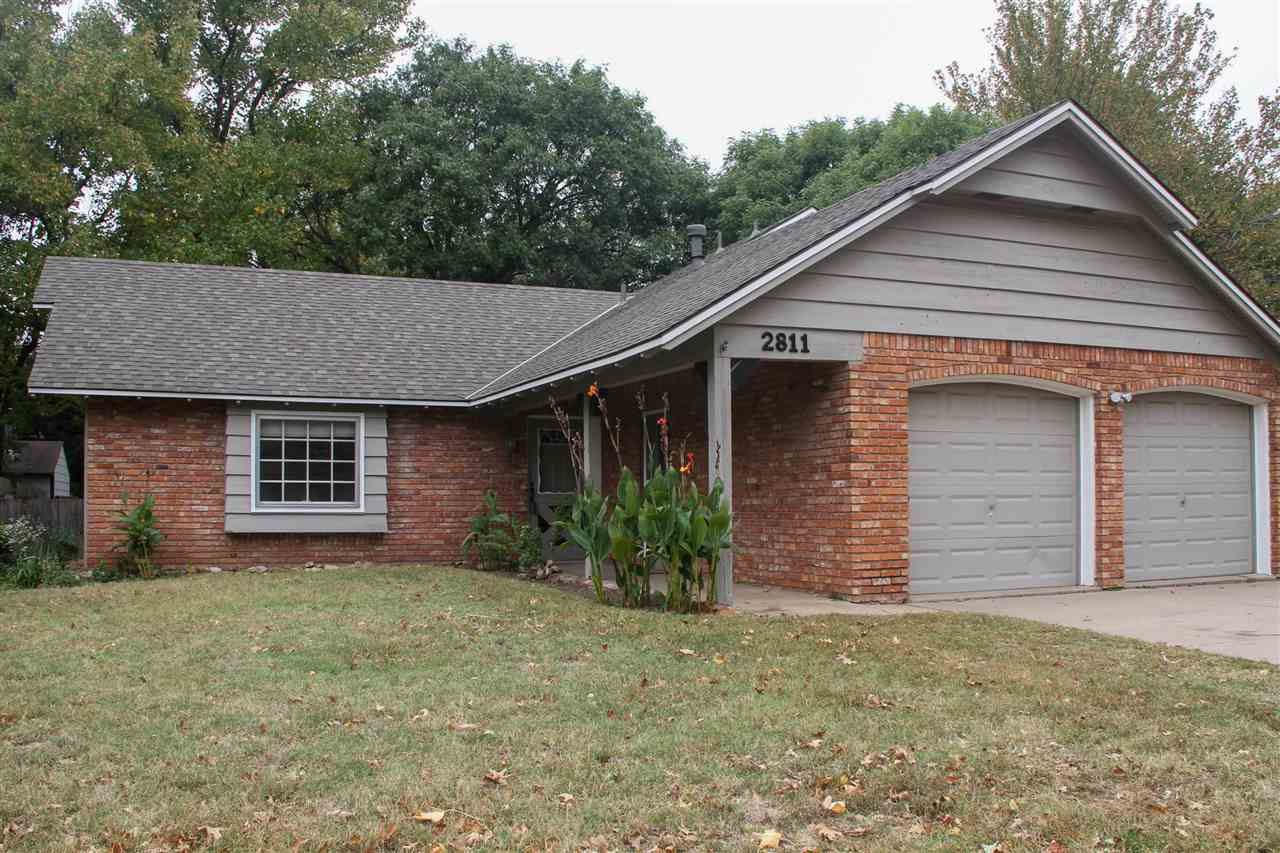 This solid brick and cedar home offers wonderful amenities. The brick fireplace in the family room i