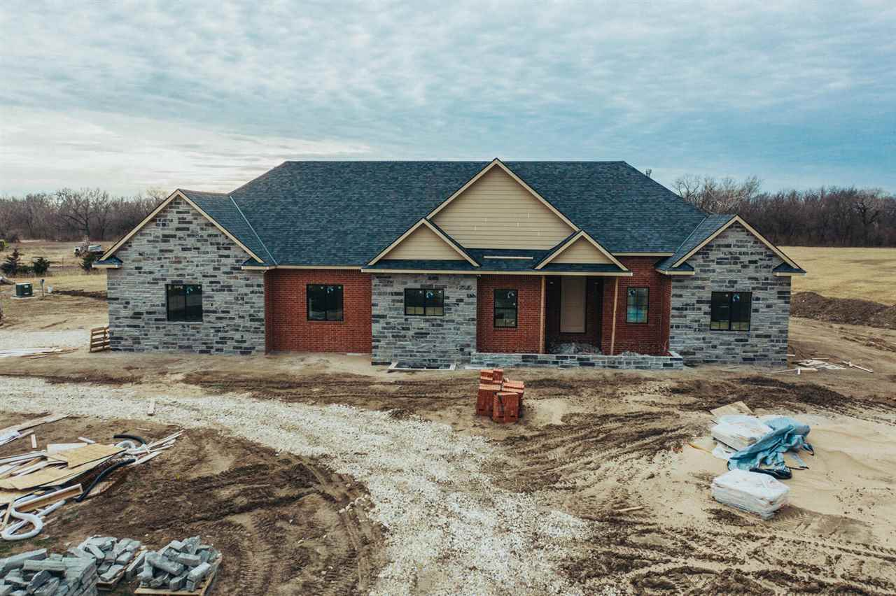 Hard to find fully fenced 21.8 Acres just North of the Wichita city limit line with 3 axilliary pastures, trees and lots of wildlife! Brand new build to be completed in Feb 2021.  Over 4600' - Perfect for your growing family.  5 bedrooms, 4.5 baths.  Plans include the exterior to be painted white (including brick) and black accents, natural stone and black windows. Circle drive, sprinkler system on irrigation well.   Soaring 10' ceilings throughout!  Split bedroom plan - master has ensuite with separate tub.  The walk in shower is  the size of a small room!  LVP floors throughout.  The main floor also has a designated office, large walk in pantry, large island in the kitchen with granite. Plenty of space in the basement family room to entertain with additional game room area and wet bar.  2 more bedrooms with bathroom.  Also includes a bonus room in the basement.  The entry from the garage has a large landing - room for extra freezers and/or refrigerators in close proximity to the kitchen. The guys will love the HUGE 3 car oversized garage!  Over 1500' with extra storage space, wash sink, hook ups for tv, separate full bathroom that also has access from the backyard!  What a man cave! The whole house including patio is wired with Cat 6 in every room for whole house entertainment wireless home audio management including external speakers.  Valley Center schools.  Close to 96/235/Meridian interchange to get anywhere fast. ***Seller would be willing to negotiate splitting up the acreage if buyer does not want full 21 acres.
