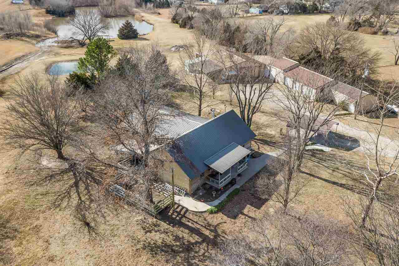 OPPORTUNITY IS KNOCKING! On the hunt for land, acreage, shops, large stocked pond and a house that the entire family can enjoy? This rare find of 12.50 acre homestead can now be yours with features you will not find elsewhere! As you walk into this home you will be greeted by vaulted ceilings, custom log features and an open concept floor plan. The living room offers a cozy wood burning stove and beautiful hardwood flooring. The kitchen is nice sized and offers an eating bar and is truly the hub of this home as it is open to the living room, dining, and family room allowing the chef not to miss out on a thing! The large family room offers an amazing view of the gorgeous property out the large bay window! Additionally on the main level there is the master bedroom, laundry room, and recently remodeled hall bathroom! On the upper level you will find two more nice sized bedrooms and second full bathroom! Outside is where you will find several large Wick and Morton buildings perfect for storing cars, large enough for a lift, equipped for welders or any other hobbies you could desire! Is your hobby more than a hobby and you want to run an at home business this property? This property has an office ready and waiting for you! Not only do you have the large buildings there are also two horse stalls, and lean-to ready for your animals! A brand new well house was recently added (120 ft deep) to the property and never been used just waiting for a new owner to take advantage. As if that wasn't enough there is a large pond that is fully stocked with bass, catfish, perch and more ready for you and your family to enjoy fishing at your own pond! This is the perfect setting to host any family gathering and truly has something for everyone! The possibilities are endless with this property. Call listing agent today to schedule a private showing today!