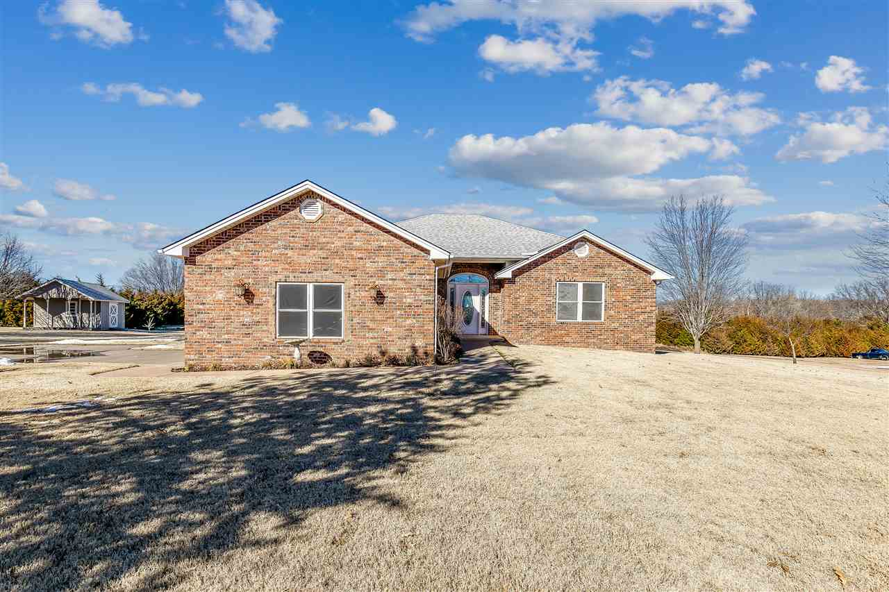 LOCATION, LOCATION, LOCATION! This one owner custom built home is located outside of city limits East of Ark City, offers over 3200 sqft and set on 1.70 acres! You will immediately fall in love with the all brick exterior, and nicely maintained landscape. Inside you will find an open concept floor plan with large kitchen and dining space open to the living room! The split master offers spacious retreat complete with master bathroom, walk in closet and private deck! With two other large bedrooms and full hall bath there is more than enough space for everyone! Additionally, on the main you will find a nice sized office and a upper level laundry. The full finished walk out basement offers a completely separate living space (perfect for teens or multi family housing) complete with a full kitchen, separate laundry, large living room, a second master suite and two additional bedrooms. Outside and you will find a large backyard perfect for summer cook outs and entertaining! Finally the two car attached garage and an additional outbuilding for storage complete this amazing property.