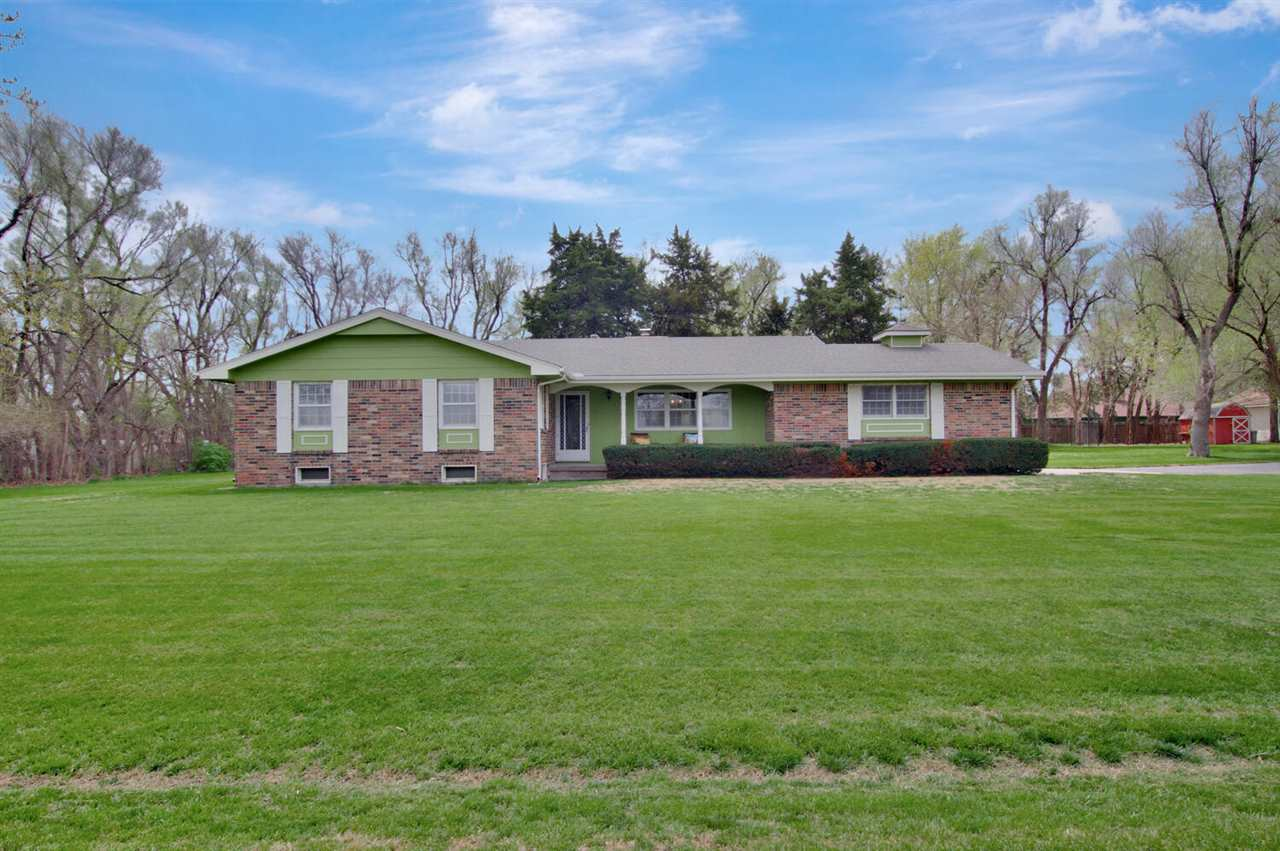 Country feel with convenience to everything in West Wichita-1.71 acre wooded lot ranch home in Maize Schools. This one owner brick home is your serene oasis. No  specials, 31 x 20 detached garage/workshop with electricity and gas heat, 43 x 40 barn, dog run/dog house and full tennis court concrete pad to do as you wish. As you enter the home the oversized living room features a picture window to your private backyard and a focal point all brick fireplace. Lots of room for family and friends to gather in this large scale living room. Kitchen is convenient to living room and dining room and has walk in pantry, plenty of counter space and is adjacent to the dining room. Dining room also has a picture window with views out back, door to backyard and a few steps to the fabulous covered patio. Master bedroom has full bath/shower, large walk in closet and room for king sized furniture. Two additional bedrooms, full bath with tub/shower and storage are also on the main level. Basement is unfinished and offers storage and great potential to finish additional living space. Covered back patio spans the length of the home and is the perfect spot to relax and enjoy nature or entertain. Majority of the yard is on sprinkler and well and is partially fenced. With some buyer repairs the full sized tennis court concrete pad could be RV parking, pickle ball court, basketball court, new building or play area for outdoor fun. Barn has storage and capacity for all of your projects, workshop/detached garage has electricity, gas heat and two roll up doors. Location is convenient to shopping and restaurants at New Market Square, hospitals, schools, Eisenhower Airport and highways. Welcome home! Home being sold AS IS.
