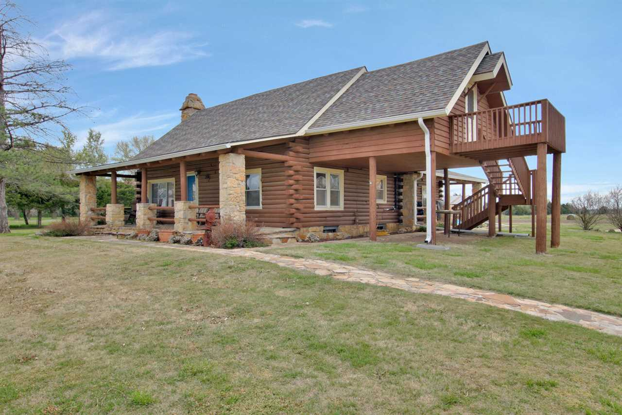 One of a kind log cabin on almost 10 acres so close to amenities of the city but still out in the country.  3 bedroom, 2 bath, 1 1/2 story home with so much character.  Main floor has 1 bedroom, totally updated bathroom, wet bar with granite and wood stove that is fully operational.  Kitchen was remodeled top to bottom with new cabinets, flooring, granite, backsplash, sink, faucet, lighting, microwave, dishwasher, range/oven and is beautiful.  Also has a large walk in pantry.  Large living room with woodburning fireplace and beautiful vaulted ceilings open to loft area upstairs.  Upstairs is a loft overlooking living room, large master bedroom and a gorgeous master bath with onyx shower, granite counters and totally remodeled.  Additional unfinished room could be sitting room, office or whatever you like.  The basement is a walk out and is unfinished but has a partially finished 3 bedroom.  Laundry is in the basement and also a partially plumbed bath.  The property has a wrought iron fence with gate in front.  The property has a gazebo for fun and entertaining with a fireplace and electricity.  Also theres a 2 car garage, large 4 stall storage building large enough for RVs, very nice chicken coop, additional buildings for storage and  last but not least is a darling play house for the kiddos.  So many updates and improvements made by the seller they include a tankless Rinnai propane whole house water heater, Northstar water softner, new sump pump, water powered backup sump pump, lift pump station, lift pump just to name a few.  Septic is only a couple of years old.  2 great porch areas to sit and relax and enjoy the peaceful Kansas sunsets, don't miss out on this gem!
