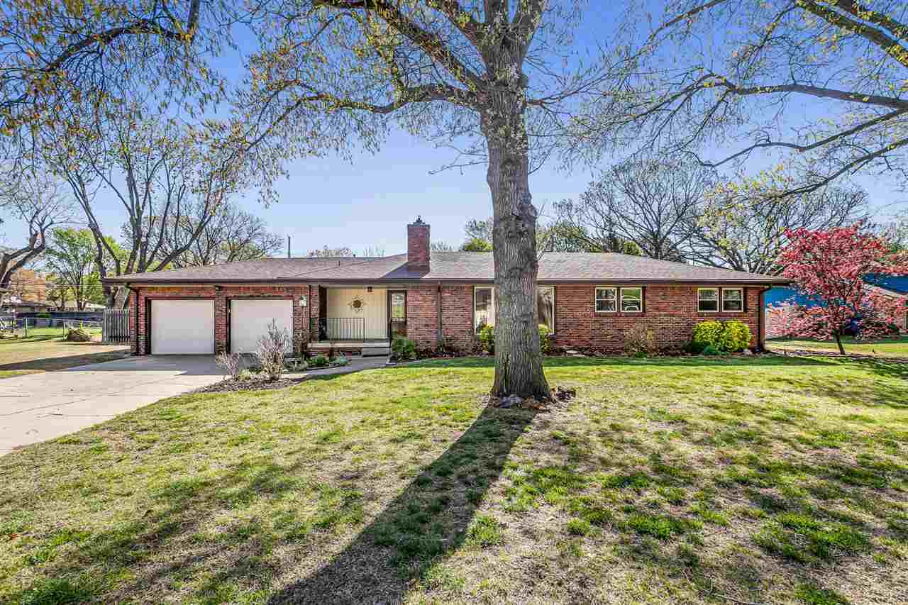 Don't miss this beautifully updated 3 bedroom 2 bath home in west Wichita.  HVAC *new* in 2019 and 50 gallon water heater *new* in 2017! The all-brick home is situated on a large 0.39 acre lot with two car attached garage.  Inside you'll notice the brick fireplace, refinished hardwood floors, spacious living room and formal dining room, knockdown ceilings, and large picture windows.  The kitchen/informal dining room is updated with granite countertops, tile floors, and the appliances are included.  Main floor laundry, three bedrooms, and 2 baths round out the first level.  Check out the retro tile in the main bathroom! Downstairs, find a decorative fireplace and sitting area, dry bar (mini fridge stays), and entertainment area with surround sound hookups. The rest of the basement is devoted to storage that could double as a workshop area or hobby room.  Take the french doors from the formal dining room to the patio out back.  The completely fenced backyard is expansive.  The shed will keep your tools and toys tidy, and there's plenty of room to garden, watch the kids or pets play, and enjoy life!
