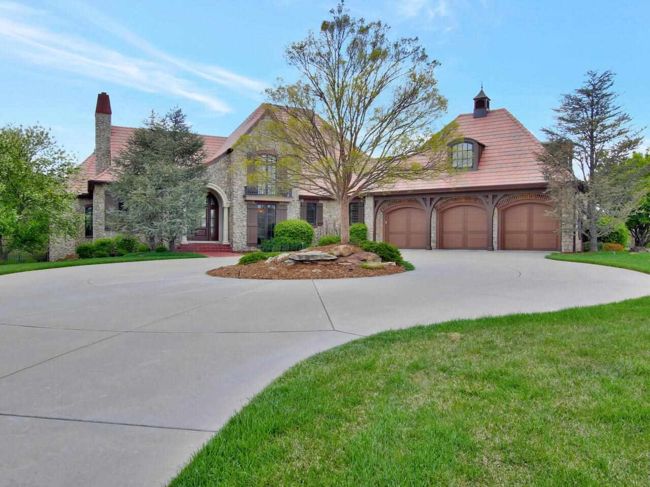 This spectacular French Country style estate home built by Van Buskirk has over 6,200 SF and is located on a beautifully landscaped 1.24 acre lot.  The property is part of a cul-de-sac of 12 incredible homes inside the gated and prestigious Flint Hills National development.  An exceptional level of architectural detail can be found both inside and out, beginning with the full stone exterior, the bronze metal work over the dormers and near the stone fireplace, the Bellaforte-Sonora DaVinci roof and the front entry which features brick steps and cast stone columns.  As you enter the foyer, your attention will immediately be drawn to the spacious Great Room and dining area that features hand hewn cedar beams, incredible Chestnut hardwood floors, a cast stone fireplace and exceptional views of the wooded, private and fenced backyard.  The Chestnut hardwood floors extend to a stunning octagon shaped library/office with built-in bookshelves, wood beams and stone walls as well as into the gourmet kitchen that features knotty alder cabinets, Thermador double ovens and gas cooktop, custom copper vent hood, Sub-Zero refrigerator, granite countertops, pantry and a breakfast area with built-in banquette. The master suite features both exceptional luxury and convenience.  The 23x17 master bedroom includes a sitting area with incredible views of the backyard.  The master bath is light and bright with tile floors, a large soaker tub and separate granite shower and it leads to a fantastic 14.5 x 13 dressing room and closet with exceptional storage.  The Dressing Room leads to an oversized laundry area with an abundance of alder cabinets, additional pantry space, a second refrigerator and a wine cooler.  Impressive windows overlook the open staircase that leads to the lower level that features a large family room with wet bar, 3 nice sized bedrooms, 2 additional baths and an exercise room.  A spectacular outdoor living area can be accessed through French Doors in the Great Room or f