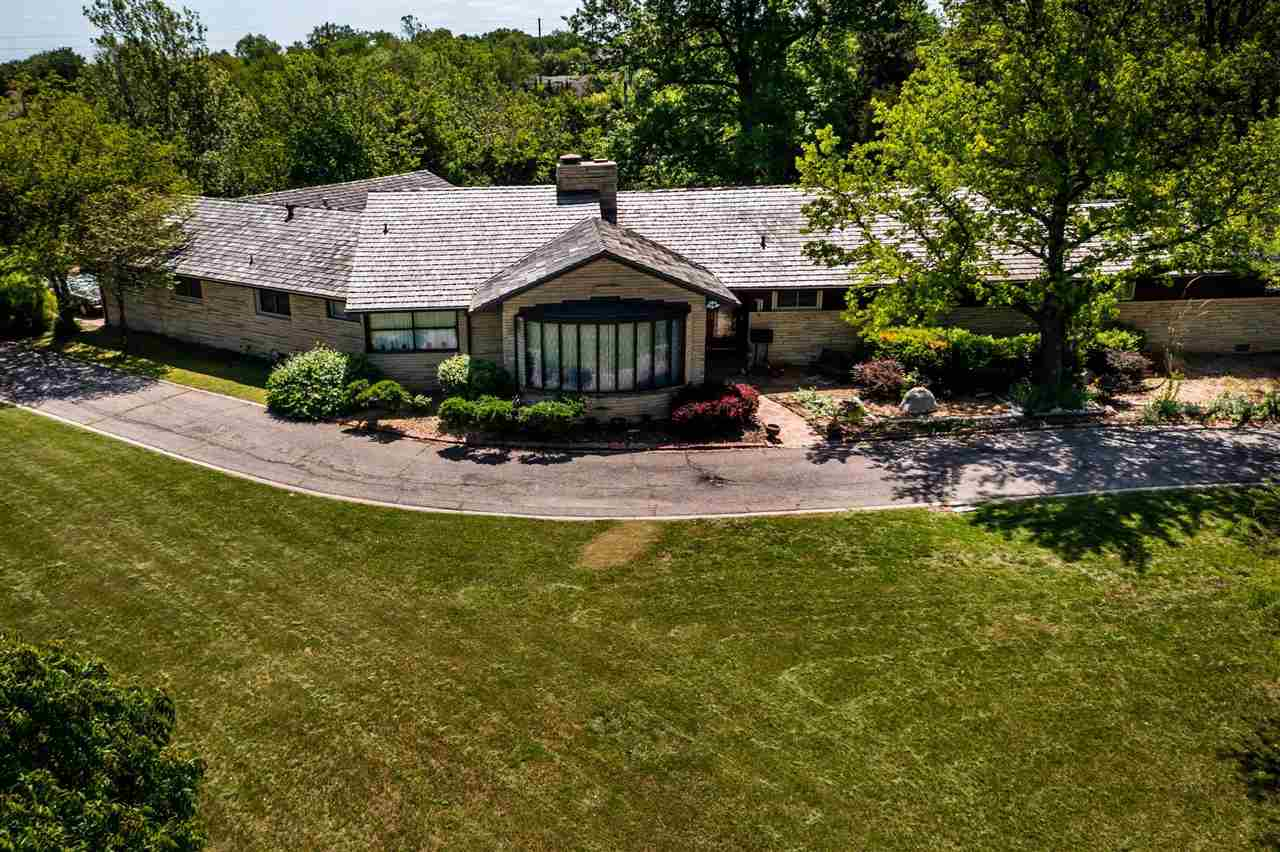 This absolutely stunning, mid century home, is located on the most breath taking piece of land with
