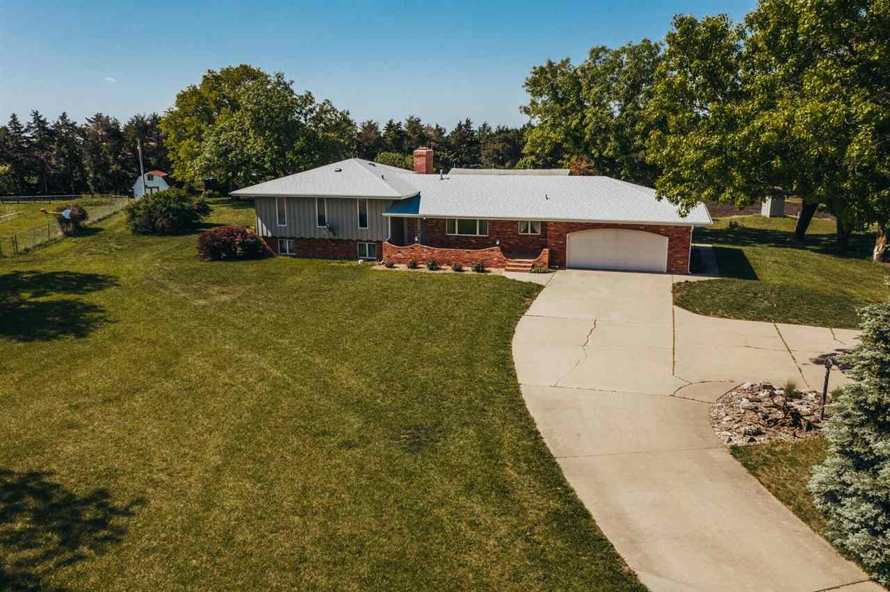 THIS IS IT!** 6.2 acres**Hesston School District**Perfectly maintained, one owner, custom built home with recent addition to accommodate handicap needs if they should arise. Everything is here to make this your home for decades! The property is just beautiful, surrounded by oak, pine and spruce trees. Lagoon and well water. All 6.2 acres is landscaped with a concrete drive all the way to 48th.  The home is primarily brick with over 4000 square feet, 5 bedrooms, 4 bathrooms (2 master suites) open floor plan with living, formal dining space and kitchen open to each other. The kitchen boasts Becker Cabinetry, recently remodeled.  All appliances, large island with eating bar and cook top. All the extras including desk area, pull outs, pantry, large drawers, appliance storage area, and more! Inviting living room with limestone wood burning fireplace. French door leads to the recent addition of a handicap accessible family room and master suite. Family room/sun room has wood vaulted beamed ceilings and gas fireplace. Master suite includes oversized walk in shower and private access to a coved patio. Huge walk in closet with built-ins. In this quad level, the upper level includes an additional master suite and two more bedrooms. The lower level has family room with a 2nd wood burning fireplace and built ins, a 5th bedroom and 4th full bath. There is also and unfinished basement with storage and concrete storm shelter.  The acreage includes an AMAZING metal ag building with separate work shop( AC/portable propane heater) and concrete floors, 2 small metal sheds, large storage shed and chicken coop. Please see property condition report for more details! Showings will start on 5/17/2021.