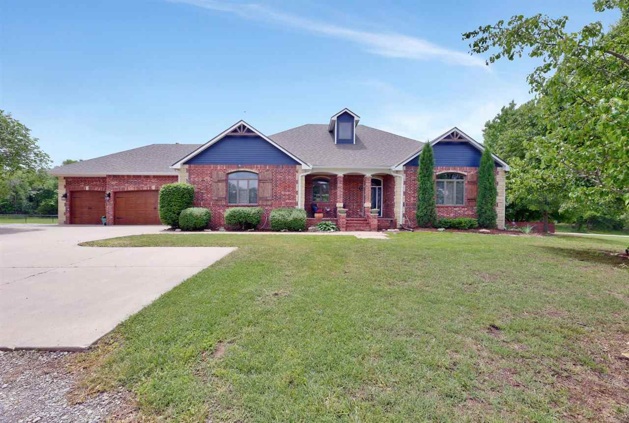 Welcome home! Your wooded private retreat in the country! Goddard schools, 5,052 sq ft home on 8.87 acres and the option to purchase additional 23.57 acres for a total of 32.44 acres for an additional cost. No specials, 30 x 72 outbuilding with 11' doors, heated in ground pool with diving board and slide, volleyball and basketball court, chicken coop, dog runs with lean too and pond-your own personal playground. Take in the peaceful quiet living with breathtaking sunrises and sunsets, abundance of wildlife, mature trees and peach, apple and pear trees in the front yard. All brick home, newer Class 4 Impact Resistant roof and gutters, newer interior paint throughout, open floor plan and this is a one of kind home. Step in and let the soaring vaulted ceilings, skylights, oversized windows with transoms and built ins amaze. The kitchen features three ovens, granite counters, wet bar, walk in pantry, island, all appliances remain and is truly a chefs delight. Living room and dining room are open to kitchen with room for friends and family to gather and enjoy the fireplace and views through picture windows. Master bedroom has detailed coffered ceiling, great living space, wood floors and door to deck. Master bathroom has been remodeled and has double sinks, granite counters, water closet, walk in closet, whirlpool tub and a newer tile shower. Main floor also features three additional bedrooms all with walk in closets and wood floors. Basement family room projector and screen remain. Full granite kitchen and wet bar in the basement and all the appliances remain. Basement has two bedrooms, full bath with whirlpool tub and tile shower. Concrete safe room is 11'11 x 7'2 and has rough in for plumbing and intercom. Laundry has large wash sink and storage. Newer composite decking on stairs, newer exterior lighting and the composite covered deck overlooks the pool and all of your amenities. Pool has new liner in 2020, new cover in 2021 and the diving board, slide and 20 x 40 poo