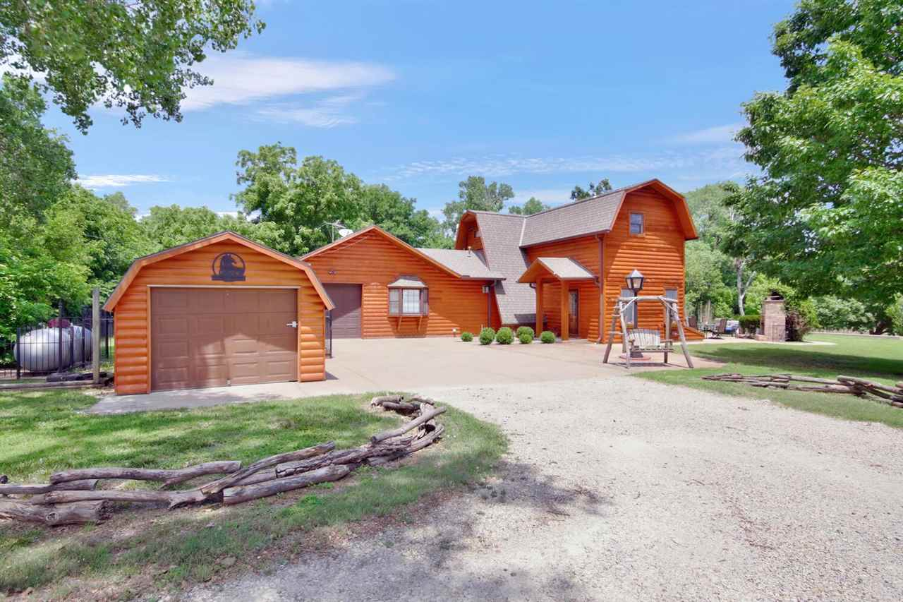 Must see! This gorgeous property on 6.1 acres is located just off of Highway 54 on the east side of Kingman. Just 30 minutes from west Wichita. This unique home shows a tremendous amount of pride in home ownership and attention to detail with custom interior work, including cedar log interior wood, antique stamped metal ceiling and hand stamped copper facing on kitchen cabinets. This home includes three bedrooms with the potential opportunity for a fourth bedroom in the finished area of the basement that includes a door/egress window. The main floor features a large, beautiful, fully updated open entry kitchen/dining room with stainless steel appliances and eating bar, living area, full bathroom, two bedrooms and a main level laundry room. The wide staircase includes a power chair lift. Upstairs you'll find the master suite with a fully remodeled bathroom including a custom oversized shower and a private balcony overlooking breathtaking views of trees and water. On the upper level there is an extra room for an office. As you head outside, the views are continuously amazing. The lake fed pond features a bridge, including lots of wrought iron fencing, deck rails and gazebo. You will enjoy the beautiful outdoor seating area with a stone fireplace and hot tub all with more views of the water and surrounding wooded areas. This property also features 2 sheds, with one serving as a workshop and a custom designed barn to complement the home. The barn includes additional garage space. There have been so many updates during the sellers ownership. Some of these updates include, newer sump pump, newer stainless steel kitchen appliances, backsplash, countertops, new lighting, sink, faucet, painted cabinets, garbage disposal, water heater, gas living room fireplace, newer Lennox HVAC unit and a newer water softener. Double throw generator, is included with the property.  Other recent additions include, a setup for horses including a lean to with tack room, wood fenced pasture and