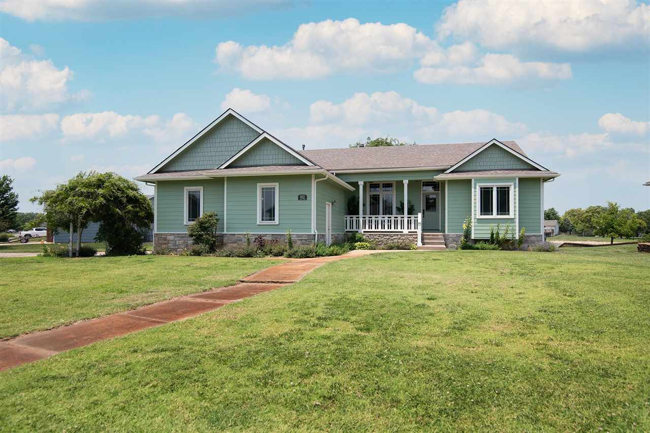 There is plenty of space for the entire family in this impeccable 6 BR 4 BA 2 Car over-sized garage sitting on an impressive lake lot in Clearwater.  You don't often find a Craftsmen style Ranch with over 4,000 finished sq ft plus get the best in small town living but close to Wichita. Great curb appeal with a covered front porch and a side porch too. Upon entering, you will notice the Craftsmen style windows and light fixtures, beautiful woodwork, Acacia Engineered Hardwood floors throughout most of the main level including the Living Room, Formal Dining Room, Kitchen and Hearth Room. The large kitchen will please the chef in the family with built-in China hutch, walk-in pantry, island, eating bar and a breakfast nook outfitted with built-ins and countertop. This is all open to the Hearth Room. Kitchen appliances stay except for the refrigerator. Glass French Doors welcome you into the office/second bedroom.  The private Master Suite sports a door to the backyard deck. Two sinks in separate vanities, soaker tub, separate shower, water closet, linen and walk-in closet are in the big Master Bath. The 2nd BR and Hall Bath with walk-in shower are close by the Master Suite. In this split Bedroom Plan, 2 additional bedrooms with wood floors and Jack & Jill Bath are down the hall from the kitchen. The convenient laundry room is just off the kitchen. Still more living space is available in the view-out lower level featuring a large Family Room sporting lots of built-ins and shelving, Game Room and spacious wet bar, all with luxury vinyl plank flooring. Two more large bedrooms (5 & 6) with the 4th Full Bath on this basement level. One of the Storage rooms was set up for a workshop including air compressor connections. Another Large storage Room is designed as concrete Storm shelter. Entertain on the covered deck with composite flooring featuring stunning lake views. Sprinkler system, irrigation well, Hardy Board siding with fresh paint.  GeoThermal HVAC with humidifier, Rev