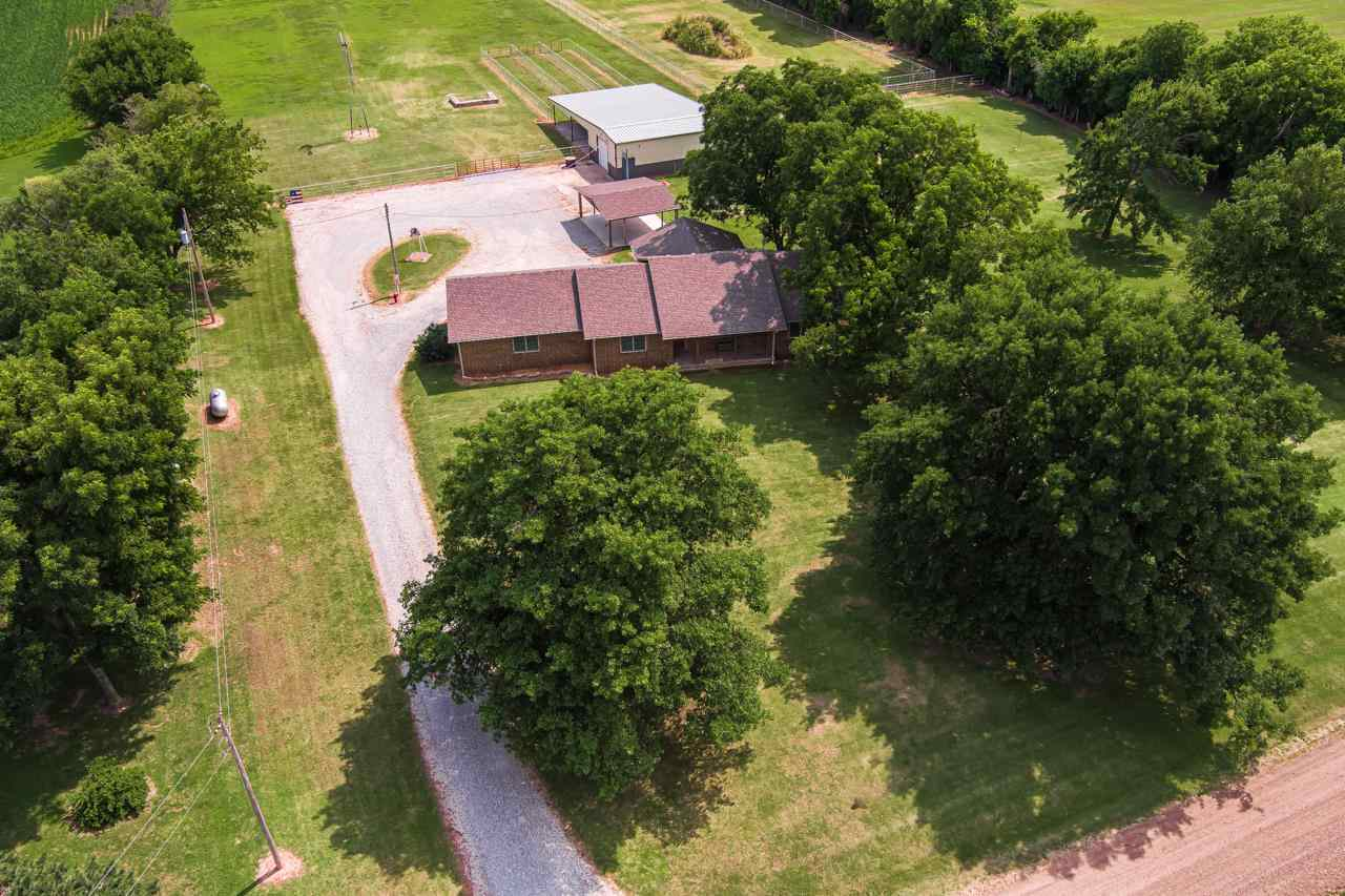 Equestrian dream is WAITING FOR YOU! This custom built one owner all brick ranch is set on 9.7 acres and is perfectly suited, fenced and ready for you to move in and bring your horses or other livestock! The house is equally as pleasing as it is very well kept and you will feel the pride in ownership from the moment you arrive! The large living room is very spacious with plenty of space for your sectional or large television. Off the living space is an updated kitchen sure to make the cook in your family happy! Tastefully updated with granite, nice sized island, two ovens, lots of counter top space and tons of cabinets! The master suite offers private master bathroom and walk in closet and a split master floor plan! The two additional bedrooms are both nice sized with good closet space! Additionally, on the main you have a full hall bathroom, and mudroom with laundry and wash sink. In the basement you have a 4th bedroom, full bathroom, and partially finished rec room! With plenty of room for storage and a concrete storm cellar the basement has much to offer! As you head outside you will love the covered patio with composite decking and large carport! The detached shop is fully insulated and climate control with its own heat and air, it is the shop you have been wanting and it offers stalls and a lean to for your tractors and other equipment/toys! The land is great pasture and it is already fenced and ready for you! If this sounds like the home you have been searching for call listing agent today and schedule a showing!