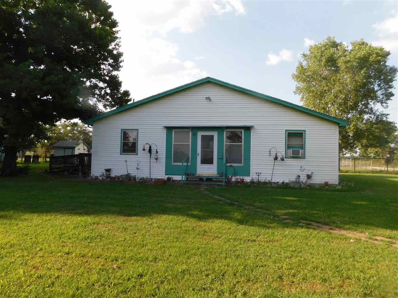 Just 1/2 mile east of the Kansas Turnpike entrance on 21st St, this property has alot to offer.  There are 2 homes, one built in 1930; the other built in 1996.  The MLS info is for the older home.  We have not had access to the newer one, but County records show it to consist of 1344 sq ft with 5 rooms (2 bedrooms) and a full basement  There is a one-car attached garage.  The land consists of rolling pasture land with a small pond and hedgerows.  There is almost 1/4 mile of blacktop frontage along the north side and gravel road on the east.