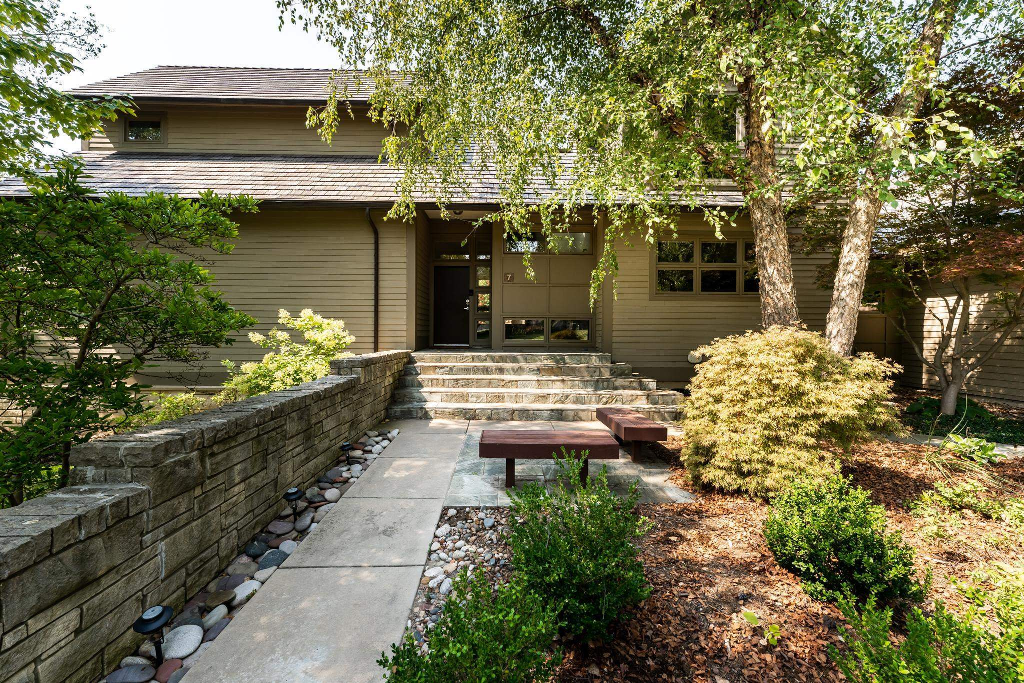 Nestled on a large, parklike yard abutting greenspace, you'll find this modern, architecturally desi