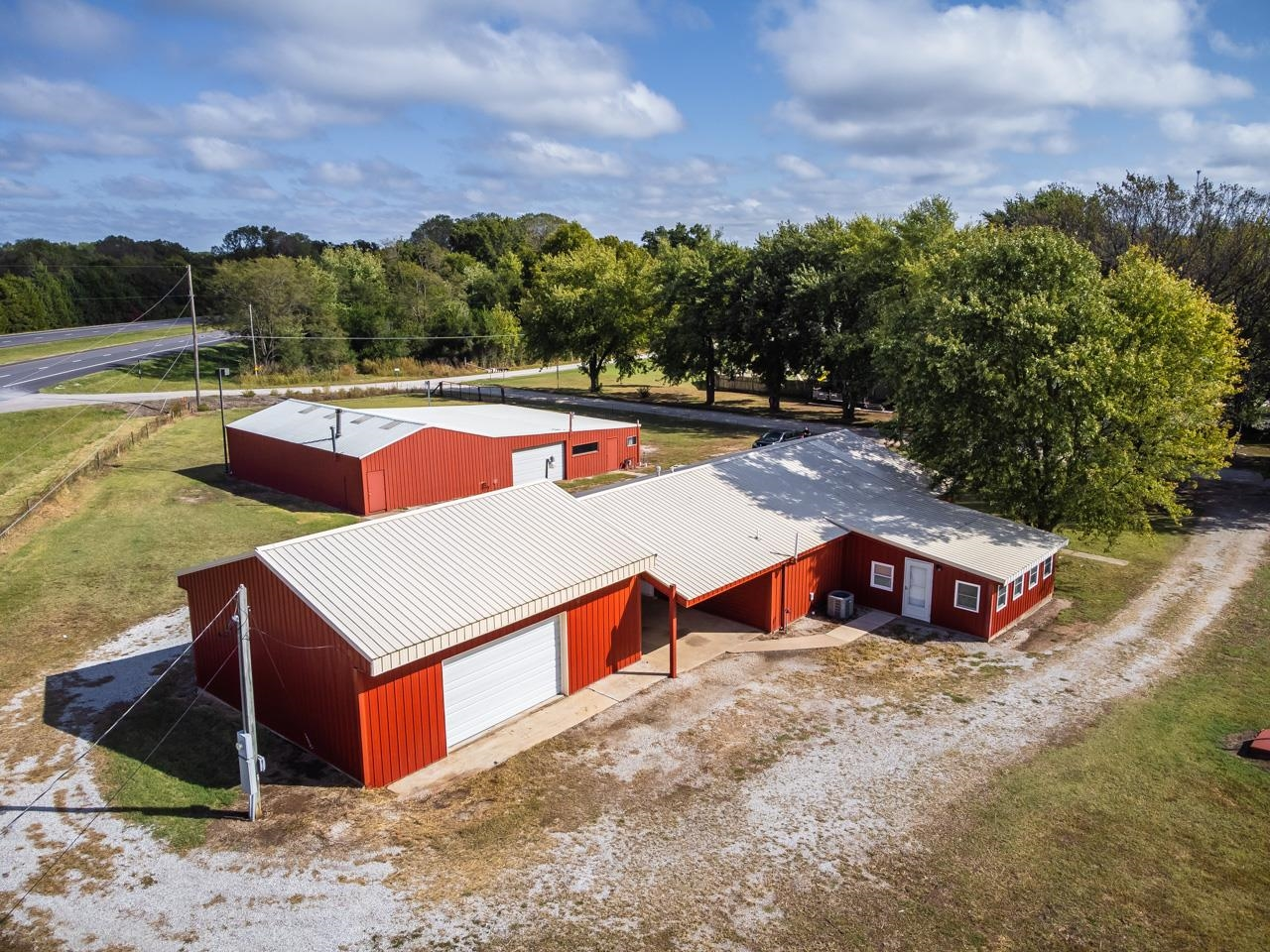 Wanting to be outside of town on a couple of acres? Need outbuildings? Want to start a business? This newly renovated property can now be yours! Updated down to the studs in 2018 this home is like new!  You will love the log exterior and perfect front porch! As you walk inside you will be wowed by the open floor plan and modern design throughout this home! The kitchen is a chefs dream with tons of new cabinetry, counter space, and new stainless steel appliances including gas range! The kitchen is hub of the home as it is open to the living/dining room! Off the kitchen you will find a large bedroom with tons of windows for nature light and separate exit. Perfect for a guest room or separate living area! Down the hall you will find the large master suite with a newly remodeled bathroom complete with a walk in shower! As if that was not enough you will love the remodeled hall bathroom and separate laundry room! Everything in this home from the plumbing, electric, central heat and air, appliance and bathroom less than 5 yrs old! Need more than 2 bedrooms? No worries! There is plenty of space to add an addition if needed. The oversized 2 car garage is complete with new electric and lighting! The large46X66 building offers bathroom, heating, 4 walk-in doors, Two 14ft overhead doors that allow for pull through access, and office area making this the perfect location if you would like to own your own business! Located on highway 77 and only a mile from town it is the perfect location! Don't miss this property and call listing agent today!