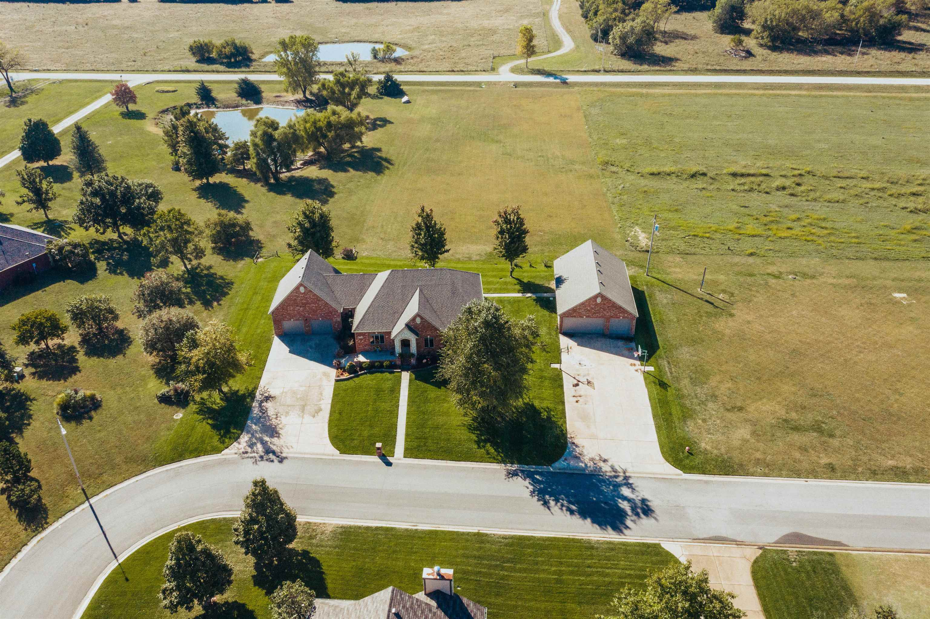 This residence has it all. Come see this spacious ranch style home nestled on 2.25 acres that includes over 4500 sq. ft. of living space. Great for families and for homeowners that like to entertain. Main floor is very open and includes multiple living rooms and multiple dining areas. Roof (2019) Class IV shingles (possible insurance discount). Basement has two large rec rooms, finished 5th bedroom with no windows, walkout to backyard and storm shelter. Enjoy the oversized 2 car garage, attached garage and the 30 x 50 detached garage that includes 1/2 bath. Easy access to the back of the lot off of the street.