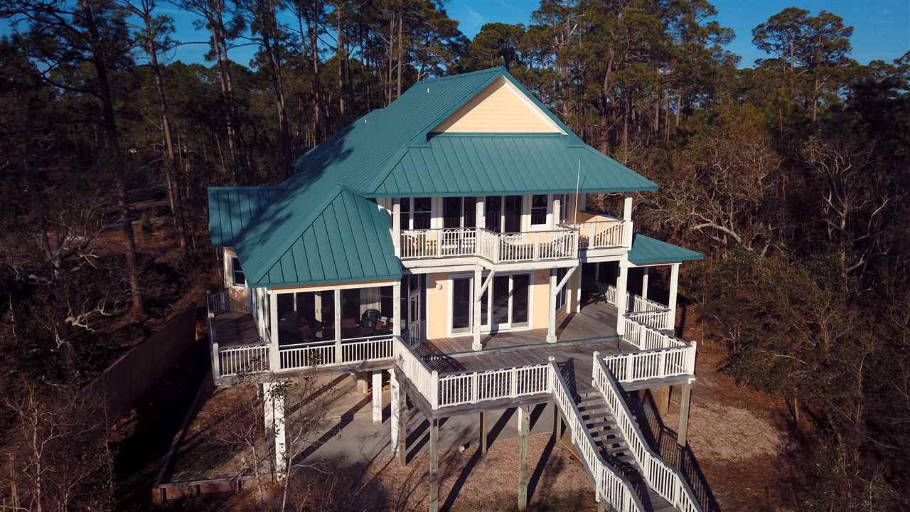 What a DEAL!!! Less than 1 hour drive from Tallahassee! The Bayfront beauty has Gulf and Bay views from every vantage point. The home has 4BR/4BA, featuring an open concept main floor, 2 decks, 1 screened porch, metal roof, and hardiboard siding. Custom woodwork throughout, large Kitchen/Dining area.  4 Master Bedrooms with closet systems. Built with an elevator shaft to service all floors and is ready for elevator to be installed. Open views of Alligator Point and the Gulf of Mexico, private amenities include 500' community dock, beach, and gated entry. Located on the East End of St. Teresa Beach in a 5 acre gated subdivision, this meticulously maintained home is a must see. Custom designed and crafted by famed builder William Solberg.  Privacy abounds in this much sought after area of the Forgotten Coast with only 3 homes in this beautifully wooded subdivision. The Perfect Getaway...Call today for your private showing. There are 2 other parcels also available with the purchase of the home for an additional price. 1 adjacent waterfront .5 acre parcel (28-06S-02W-0000-0011-0020) and 1 full acre parcel (28-06S-02W-0000-0010-0030) located across the driveway from the house.