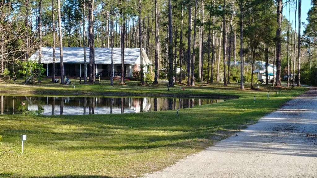 Beautiful Country Living in a peaceful setting.This large custom brick home built in 2002 by the owner is situated on 5 acres with pond in front. Located only 2 minutes from Carrabelle and Crooked River and 10 minutes to the beach. The front screened porch stretches the entire length of the home providing a relaxing and bug free view of the pond. Part of the rear porch was converted to a den with the remainder housing the laundry room and outdoor kitchen. The concrete patio and parking pad is right outside the back door providing easy entry into the home. Split plan. The beautiful master suite has a nice sitting area and large bathroom. There is a separate formal living and dining area. The kitchen is large and nicely laid out with a huge pantry and breakfast bar. The 30x60 Workshop is fully insulated with roll up doors. Room Dimensions are approximate and need to be verified by buyer.