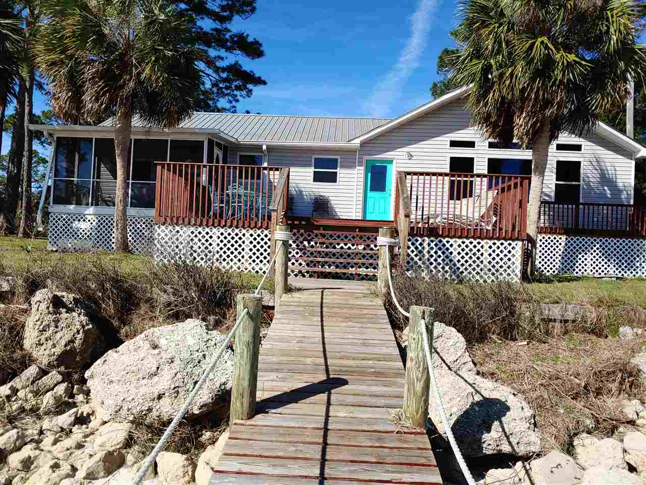 Back-up Offers Welcome - Below Appraisal - This sweet bay front cottage is located on Hwy 98 E in the quaint fishing community of Lanark and has a newly repaired dock and boat lift, great views of Bird Island, Lanark Reef and Dog Island.  The open concept and huge kitchen make it perfect for large gatherings of friends and family and boasts an over-sized kitchen island (3'x8'). There are reclaimed barnwood floors throughout the main living area, kitchen, hallway and master bedroom. The slightly white-washed knotty pine tongue and groove walls and ceiling give this cottage a comfy rustic beachy feel.  There is a large pantry and laundry room. The large deck and screened porch overlook the white sandy beach, dock and boat lift.  The large master bathroom has a shower stall, new floor, tile and toilet. The guest bath has a shower/tub, new floor, tile and toilet.  There are high vanities in both baths. The sliding door in the master bedroom has recently been replaced with an impact glass window.  The cottage has easy to care for vinyl siding, stand in seam metal roof, a separate cinder block garage with new door and opener and a new metal covered boat storage unit.  The sea wall is in good shape and no repairs were needed after hurricane Michael.  There was only minor damage done to the home which as been repaired.  The dock and boat lift suffered minor damage which have been repaired. The piers under the home were reinforced after the storm.
