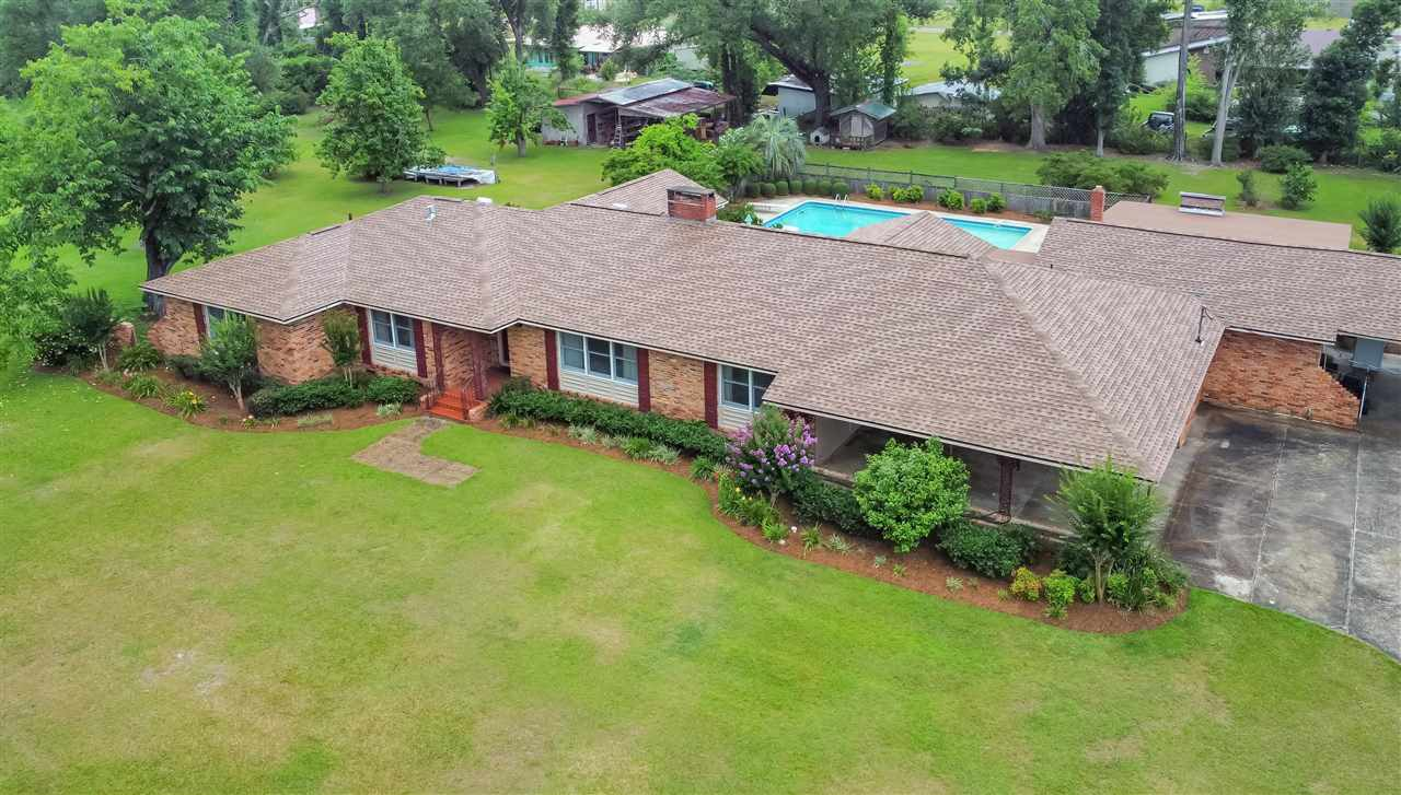 Wow! This large and meticulously maintained family home on over 2 acres features almost 5000 heated and cooled square feet of living space! These lovingly kept grounds hold fragrant honeysuckle, hydrangea, day lilies, muscadine vines, pecan and pear trees, fig trees, many citrus trees, and so much more. We also have a large barn for storage. Surrounding the salt water pool, we have ample concrete patio and deck space for entertaining! Inside the main home, we have 4 bedrooms, dedicated office space, and 4 and a half baths. The large master suite has two closets (one large walk in and one oversized closet), TWO bathrooms, and a set of lovely french doors opening to the outdoor pool and deck/patio space. This home also features two large living areas with a double sided fireplace, large formal dining room, eat in kitchen with stainless appliances, spacious laundry room with sink and plenty of storage, and two pantries! Newer wood plank flooring is featured in the kitchen and laundry. In the mother-in-law suite/bonus cottage, we have a large bedroom with bathroom, an enormous amount of storage space, and a fabulously updated living space with kitchenette. Mother-in-law suite also opens up to the pool area and could be used as a pool house for parties, guest house, or Air BnB! With a combined 5 bedrooms and multiple living areas, the possibilities truly are endless. Bring your designs and make this large estate your own!  Measurements approximate. Buyer to verify if important.