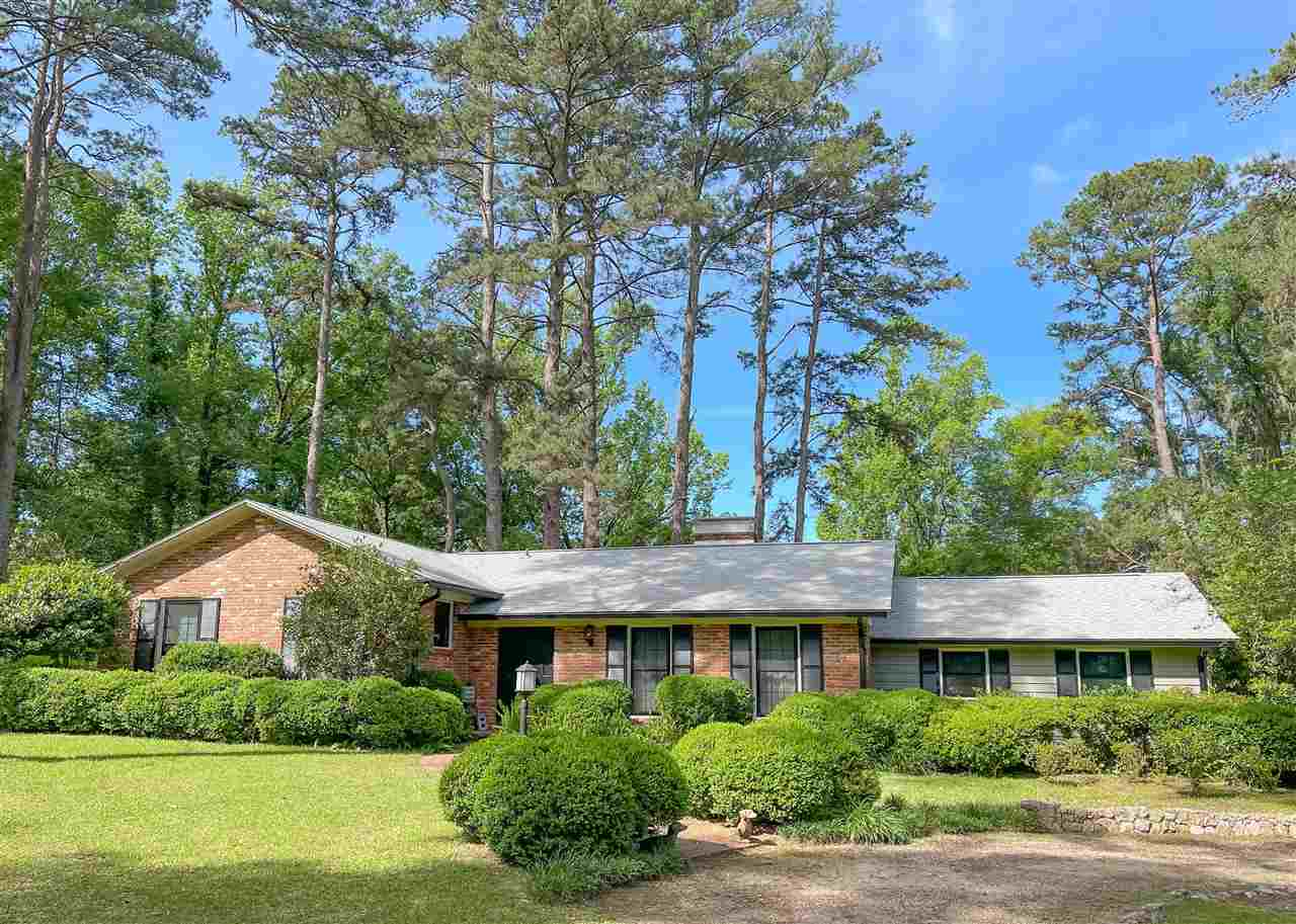 Beautifully updated all brick Carl Ferrel home on almost an acre and a half inside the city limits! This home is located in desirable Northeast Tallahassee in excellent school zones and close to everything Northeast Tallahassee has to offer. This huge lot has been meticulously landscaped for incredible curb appeal and has plenty of room for kids and pets to play. The private back yard features a well positioned patio that is perfect for entertaining. Inside the home, we have 3 spacious bedrooms with large closets plus a small bonus room and 2 full baths, eat in kitchen/dining room with a sweet bay window overlooking the meticulously maintained back yard, formal living area, huge family room, tons of storage, laundry room with included washer and dryer, and a fantastic sunroom overlooking this property's gorgeous landscaping. This wonderful home also features a stunning double sided fireplace! The incredible master suite offers french doors opening up to an outdoor covered patio, walk thru closet with barn doors, and a gorgeous tile shower with glass enclosure. Many more updates include the original refinished hardwood, luxury vinyl plank, and beautiful ceramic tile flooring. The brand new kitchen in this home includes all new appliances and durable quartz countertops. All new energy efficient windows in 2019, new roof 2017, and all appliances stay! Small storage shed in the back yard stays as-is. Come claim this perfectly updated home today!