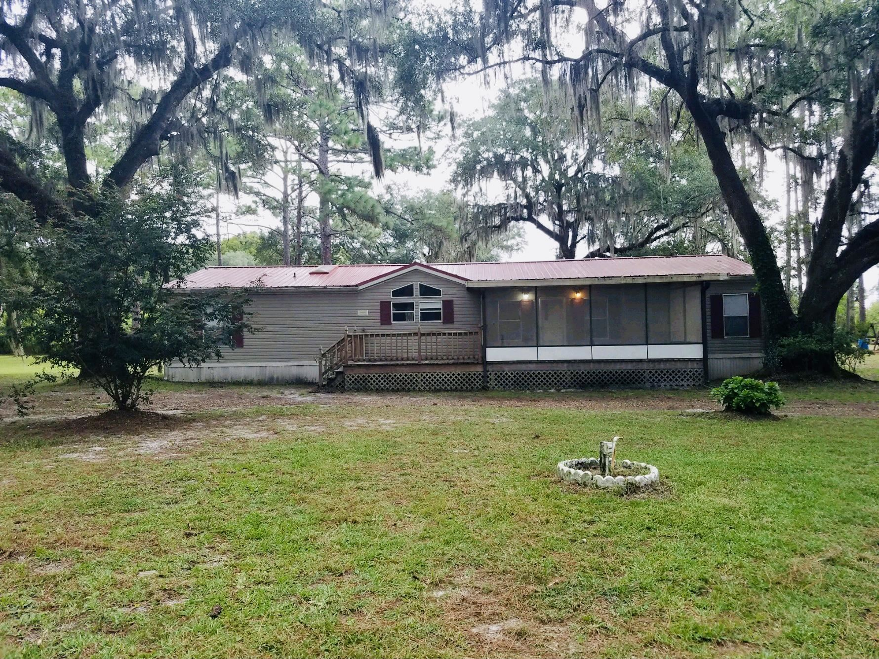 Nestled in beautiful live oaks and pines in Taylor County, this 3 bedroom, 2 bathroom, doublewide mobile home sits on a spacious 1.19 acres. This home has a long lasting metal roof put on by previous owner. New AC in 2019. Mature Loquat, Kumquat, plum and fig trees. The primary room has a grand garden tub and shower. The open concept kitchen allows for entertainment while enjoying the dining area and living room. The warm wood burning fireplace makes for a cozy feeling in the winter months. The large screened in porch is the perfect space to sit back and relax and enjoy the great outdoors. You also have an open deck area for entertaining family & friends. The large workshop has electric and plumbing and is perfect place to work on those much needed projects. The house is on city water. Behind the workshop is a chicken coop or firewood storage area. This property is a quick drive to Winn Dixie and easy access to town. This is a must see property. Seller is motivated and ready to sell.
