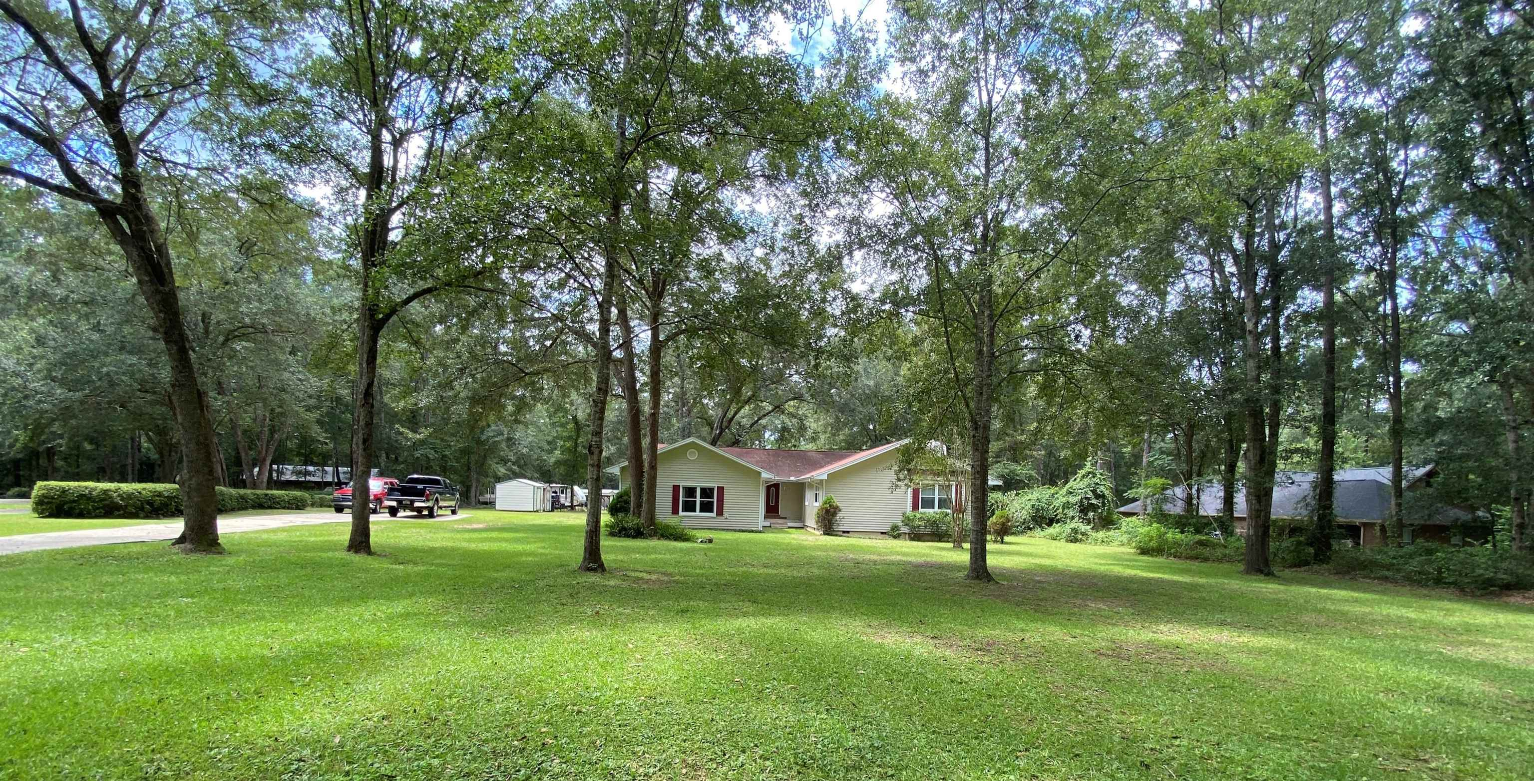 1.22 private acres with a large well maintained family home and a lot of living space and square footage  ($137 sf). RV and boat parking complete with 30 amp electrical service, two 12x20 storage buildings with electricity, covered carport shed, and other storage buildings to remain. Ample room for a pool and/or build more living space/garage. The property backs up to the Miccosukee Greenway so never a back door neighbor! The home itself has a split bedroom, 2 living room areas plus an enormous recreation/man cave/great room with gorgeous pool table and bar. Newly enclosed heated/cooled sunroom with hottub. Enormous master bedroom with updated bath and walk-in tile shower.  10,000 watt gas propane generator included. Quiet neighborhood and great neighbors!!!