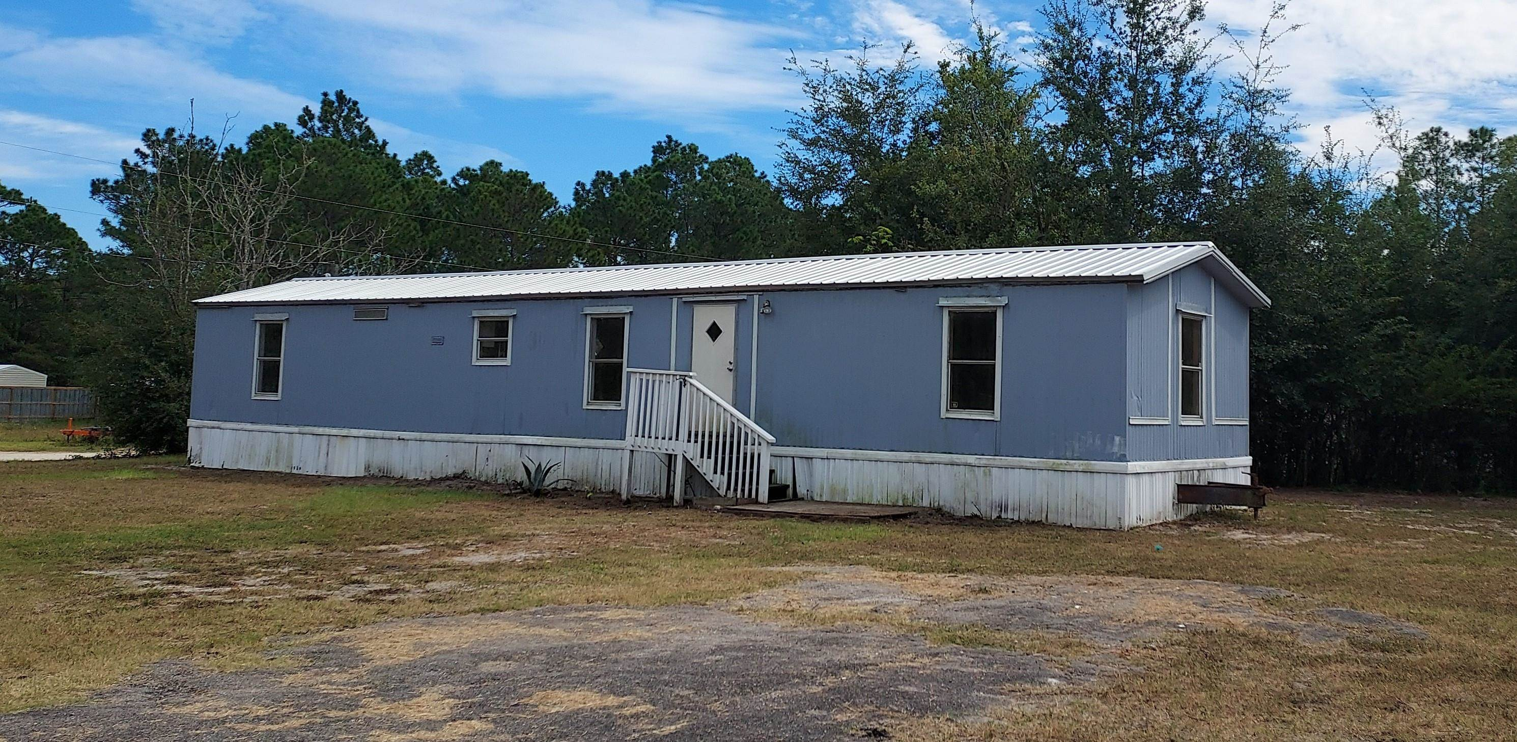 1991 14x70 Single -wide mobile home. Needs work, but has no roof leaks. Some new plywood sub-floors and vinyl flooring in 2017. New metal roof 2017. Totally renovated in 2017, but was not maintained by tenants. 2 master suites. HVAC worked when property was vacated in September 2021. Needs plumbing work in shower in west side bath. Utilities are not on. Dishwasher and Microwave Hood only, unknown if these are operational. Nice flat lot on the corner with 100' Avenue H frontage. Great for a fixer upper for vacation rental, fishing get-away or long term rental. Showing Instructions required. Dimensions are approx, must verify if important.