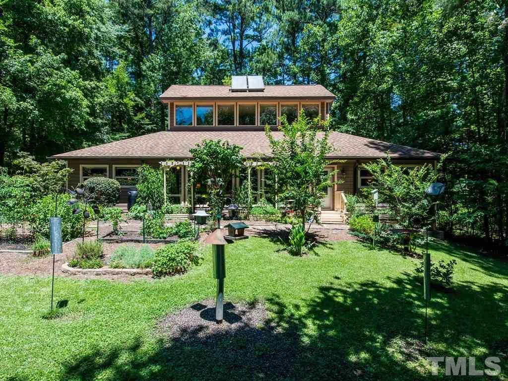 It isn't often that I am speechless on a home but this is a MUST SEE! Walls of windows in the front allow the light to cascade in & highlight many neat architectural features including brick paver flooring! 360 stunning views of your private lot enhanced by wrap around screen porch with hot tub! Many energy efficient & cosmetic upgrades! Option of dual master suites, one up & one down! Wood stove! Updates in kitchen, downstairs bath, roof, HVAC, etc! Solar panels heat water! Tucked back on cul de sac lot!