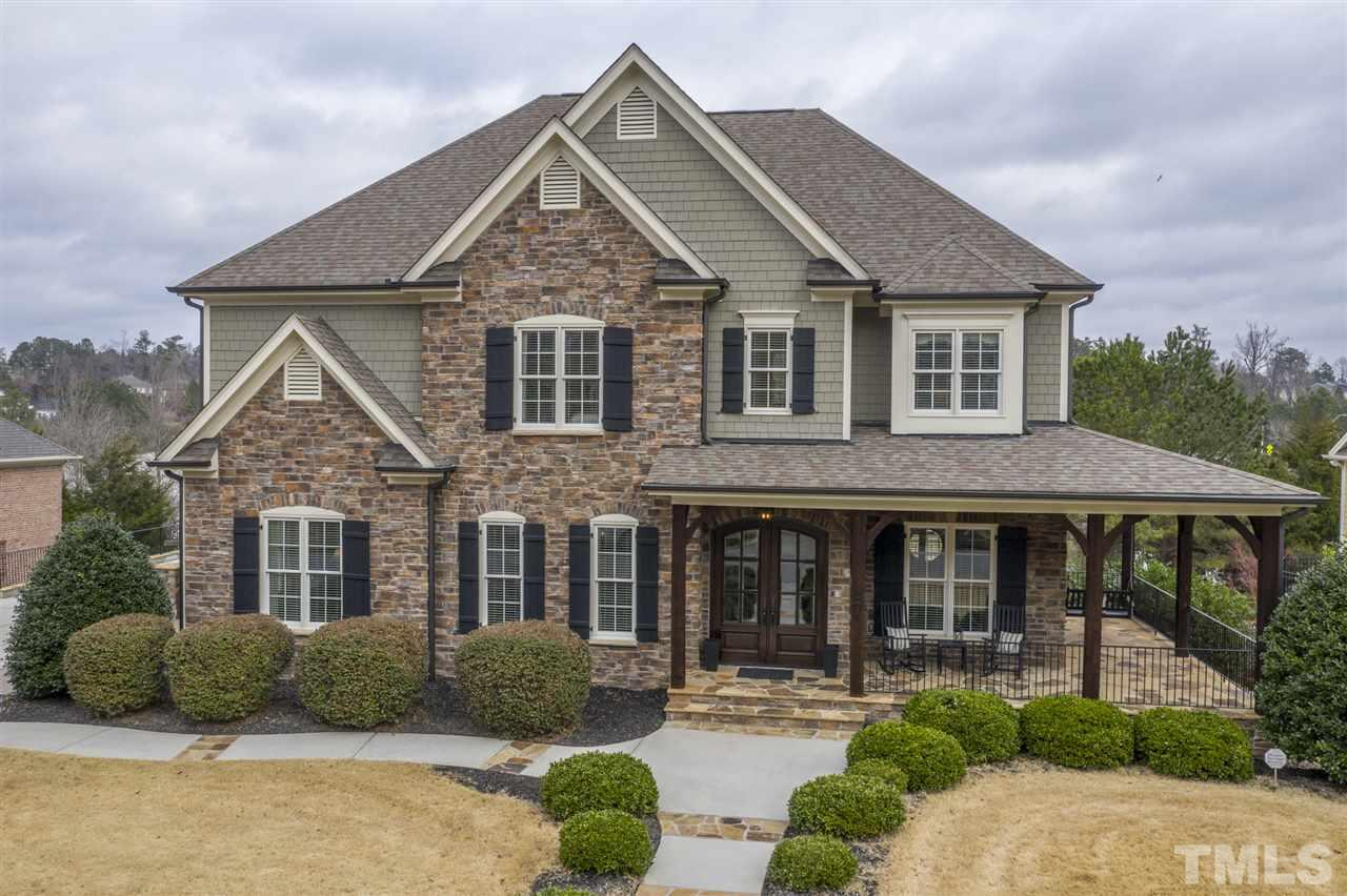 This custom home, located on Cary Park Lake, is stunning inside & out. Built-in cabinetry & millwork thoughtfully placed throughout. 1st flr features hardwoods, 10' ceilings, formal living & dining rms & executive office. Stacked stone fireplace is focal point for open family rm/kitchen area. Finished basement  features huge hearth in den, guest bedroom, media & exercise rooms. Addtl storage in basement & walk-up attic. Outdoor spaces overlook lake & include patio, screened porch & deck w/ gas line.