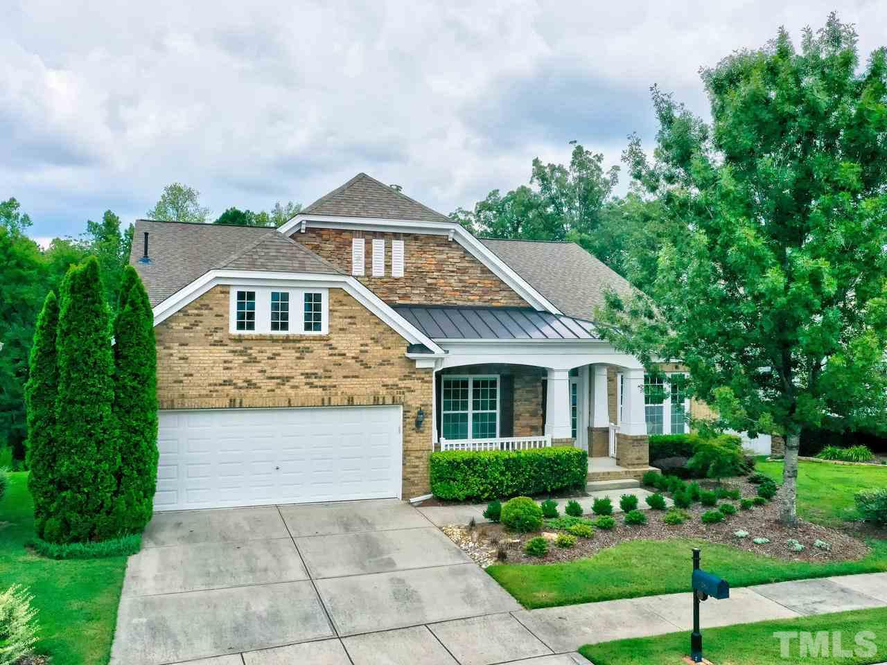 Simplicity + elegance = Fabulous! Morningside Lane model with stone and brick accents, welcoming front porch with wooded views. Yard irrigation system plus soaking hoses in plant beds.
