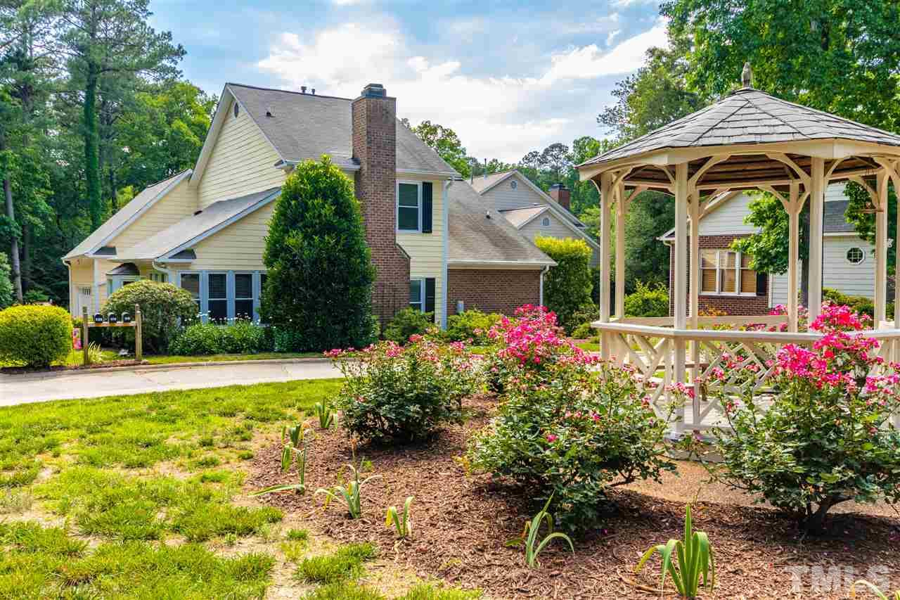 A lovely gazebo welcomes you to the culdesac that you'll call home. Vistas from the sunny living room include this rose ringed centerpiece.