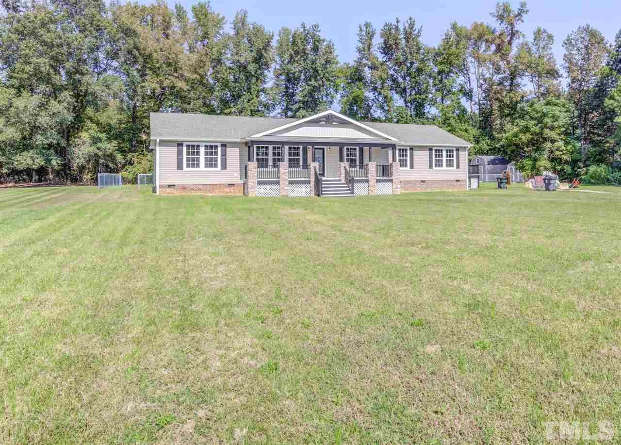 Large flat 1-1/2 acre lot with fenced backyard plus 2 storage barns & huge deck!
