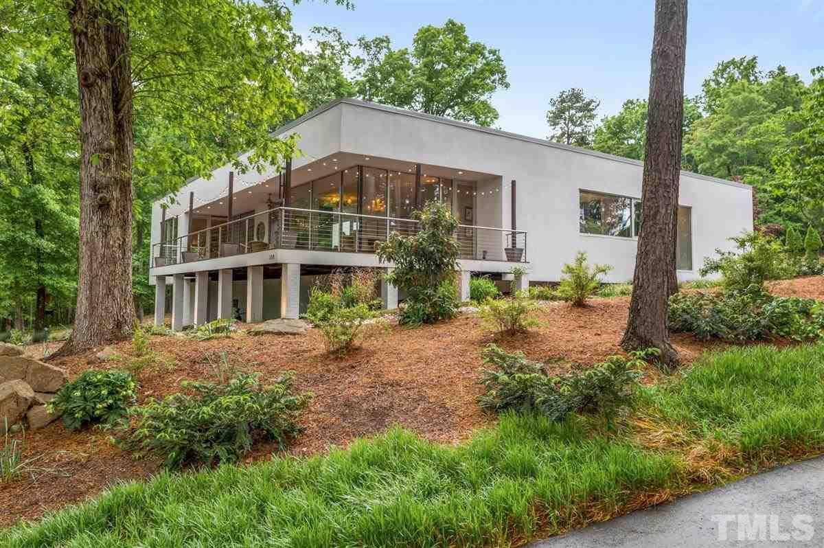 Unique contemporary on over 2.6 acres of peaceful property. You will feel like you are miles away when in fact, you are just a stone's throw from all that Durham and Chapel Hill have to offer. Designed by Philip Szostak, famed architect of DPAC, this home features views of the private courtyard or professionally landscaped surroundings from every room. Wonderful cook's kitchen that invites entertaining, flex office space, energy efficient geo thermal and spray foam- This is not just a home, but a retreat!